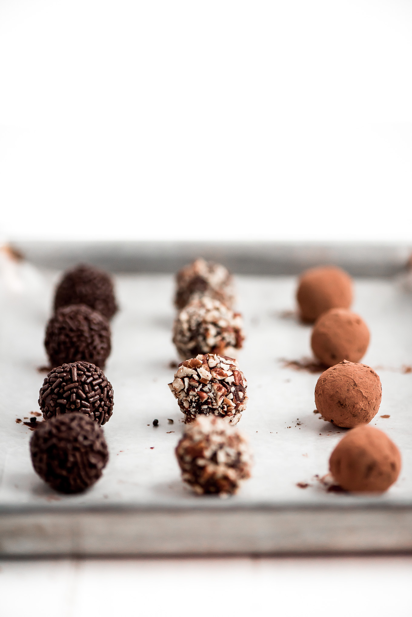 3 kinds of homemade Chocolate Truffles on a baking sheet- chocolate sprinkle, pecan, and cocoa.