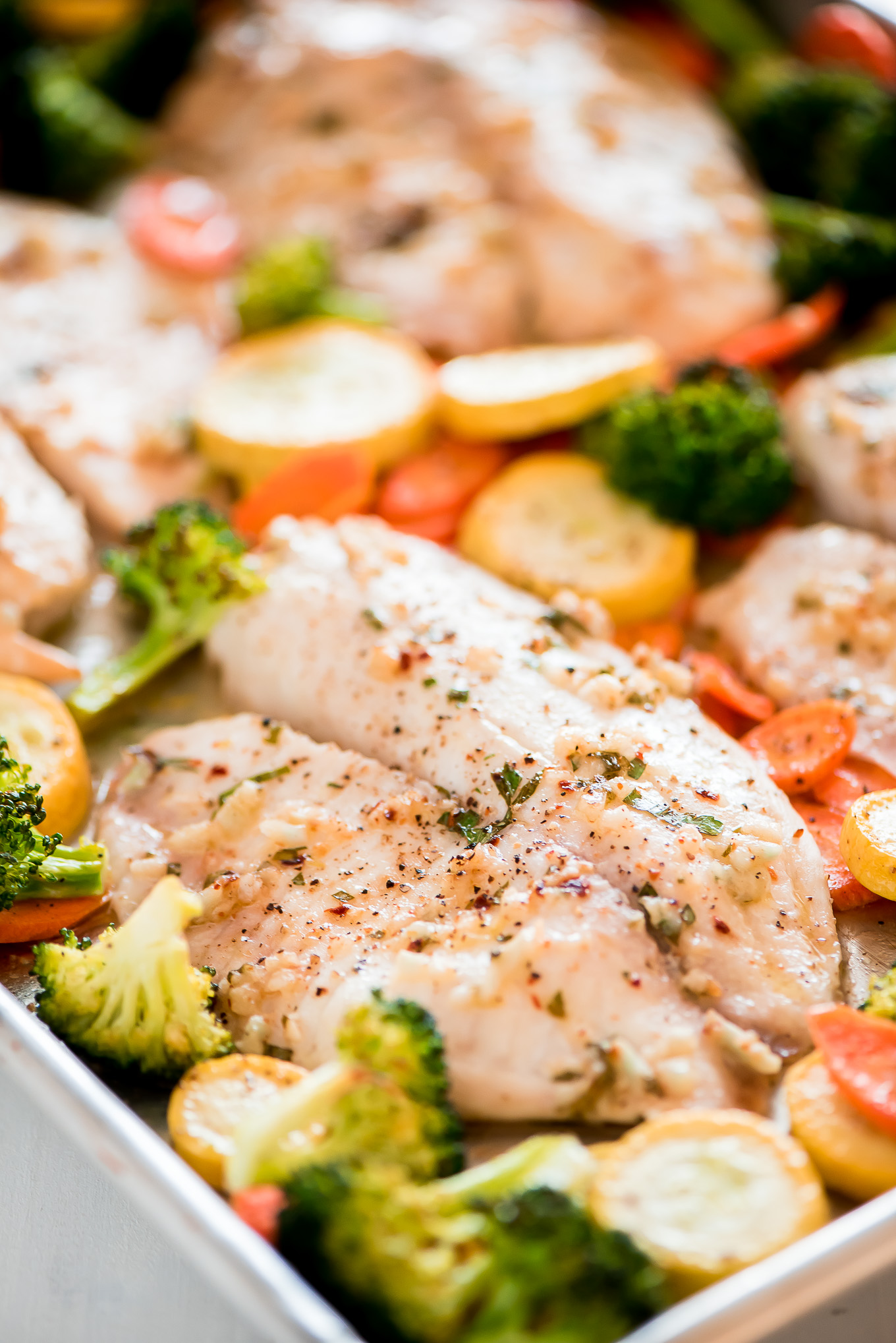 Close up of Baked Tilapia and roasted vegetables on a sheet pan.