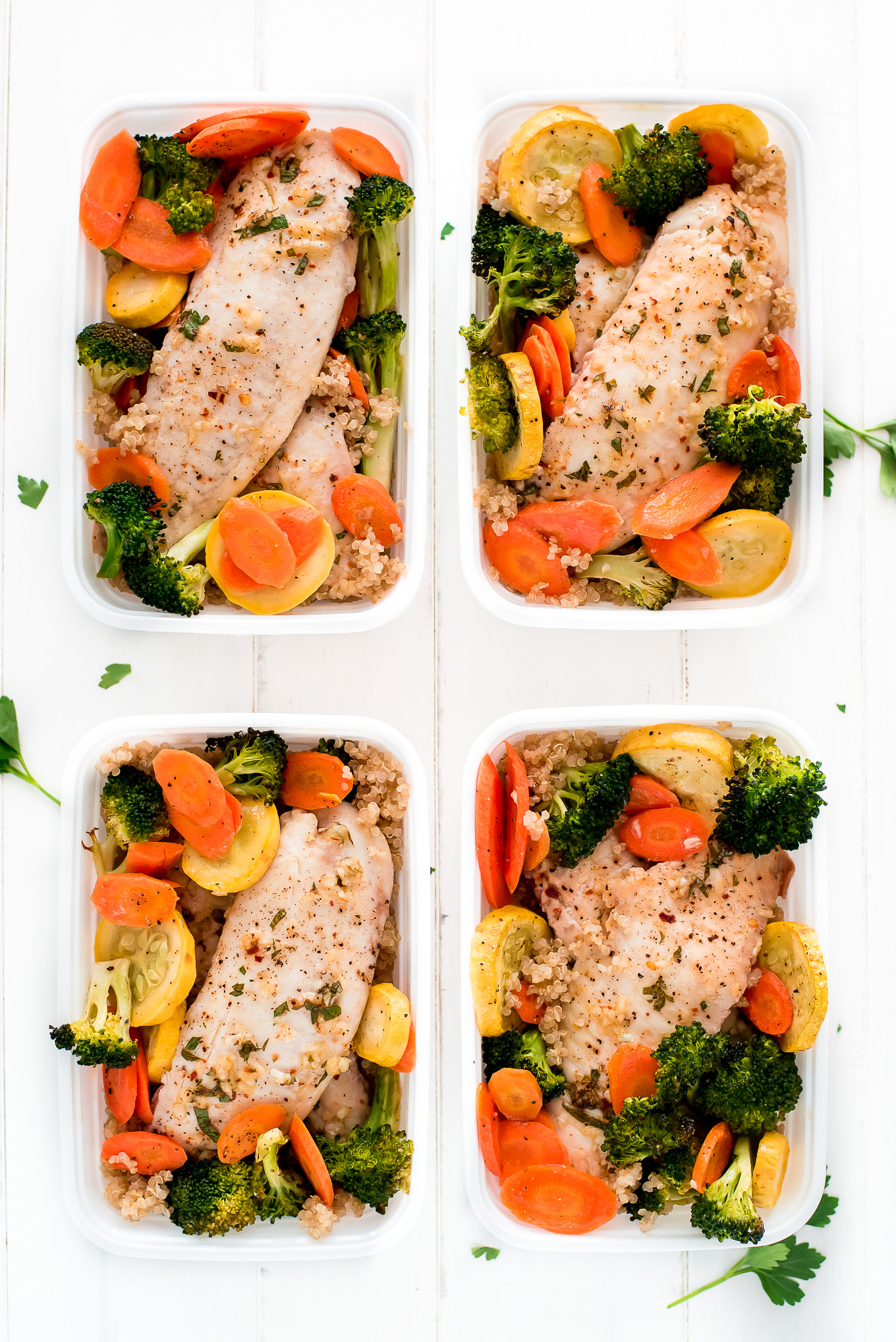 Sheet Pan Baked Tilapia and Roasted Vegetables divided into meal prep containers.
