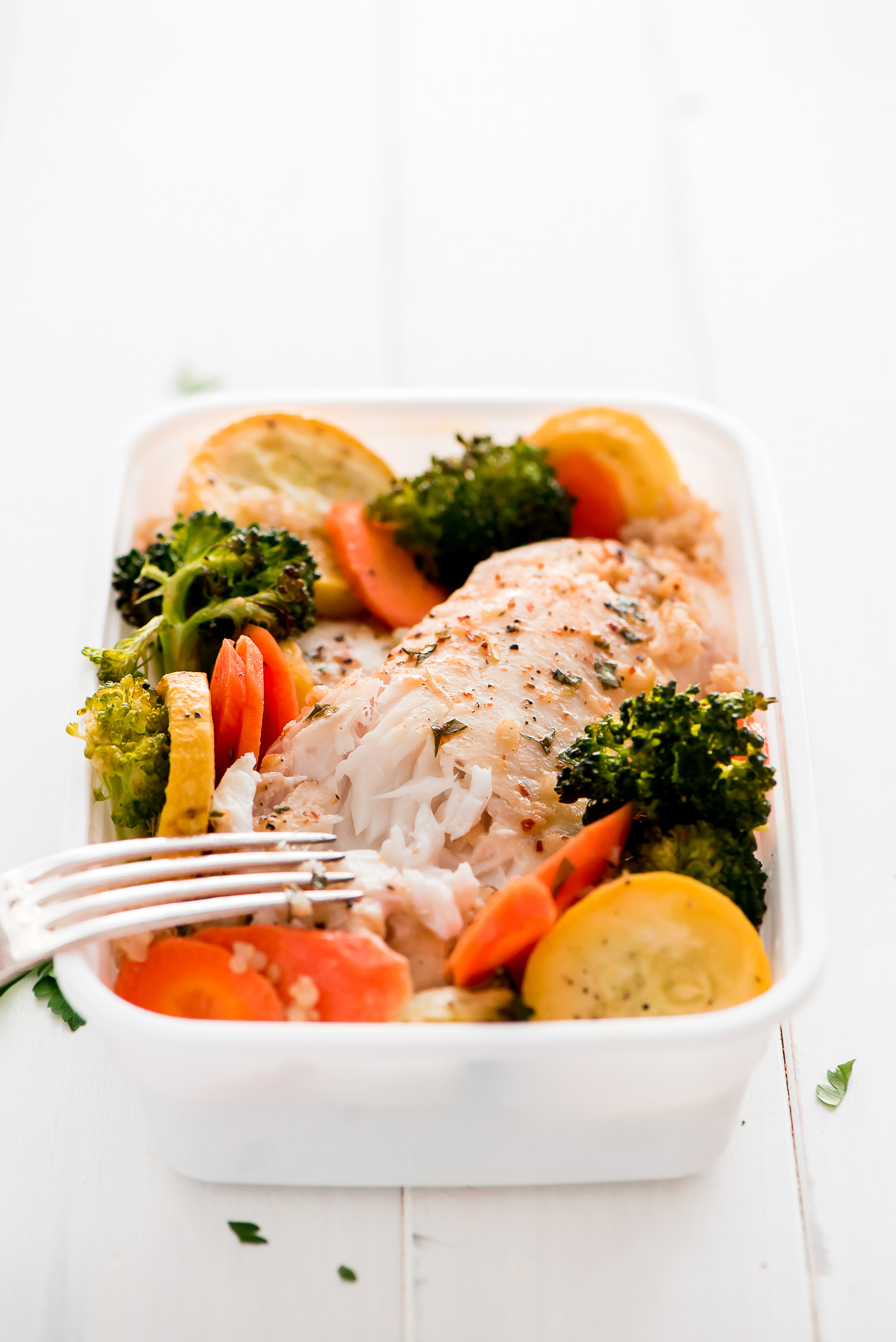 Close up of Baked Tilapia in a meal prep container with roasted vegetables and quinoa.