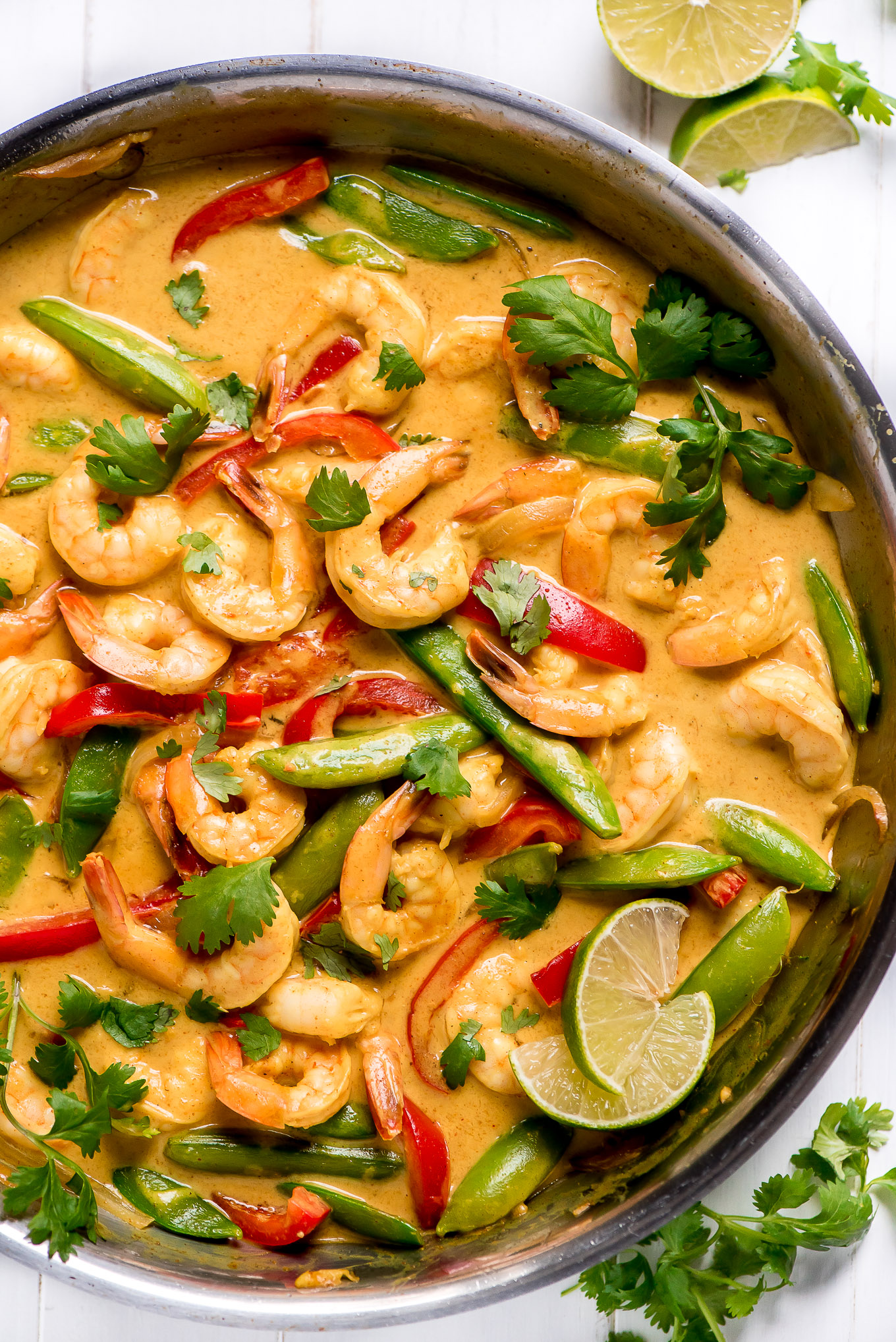 Pan of Thai Shrimp Curry loaded with red bell peppers, snap peas, shrimp, cilantro, and lime.