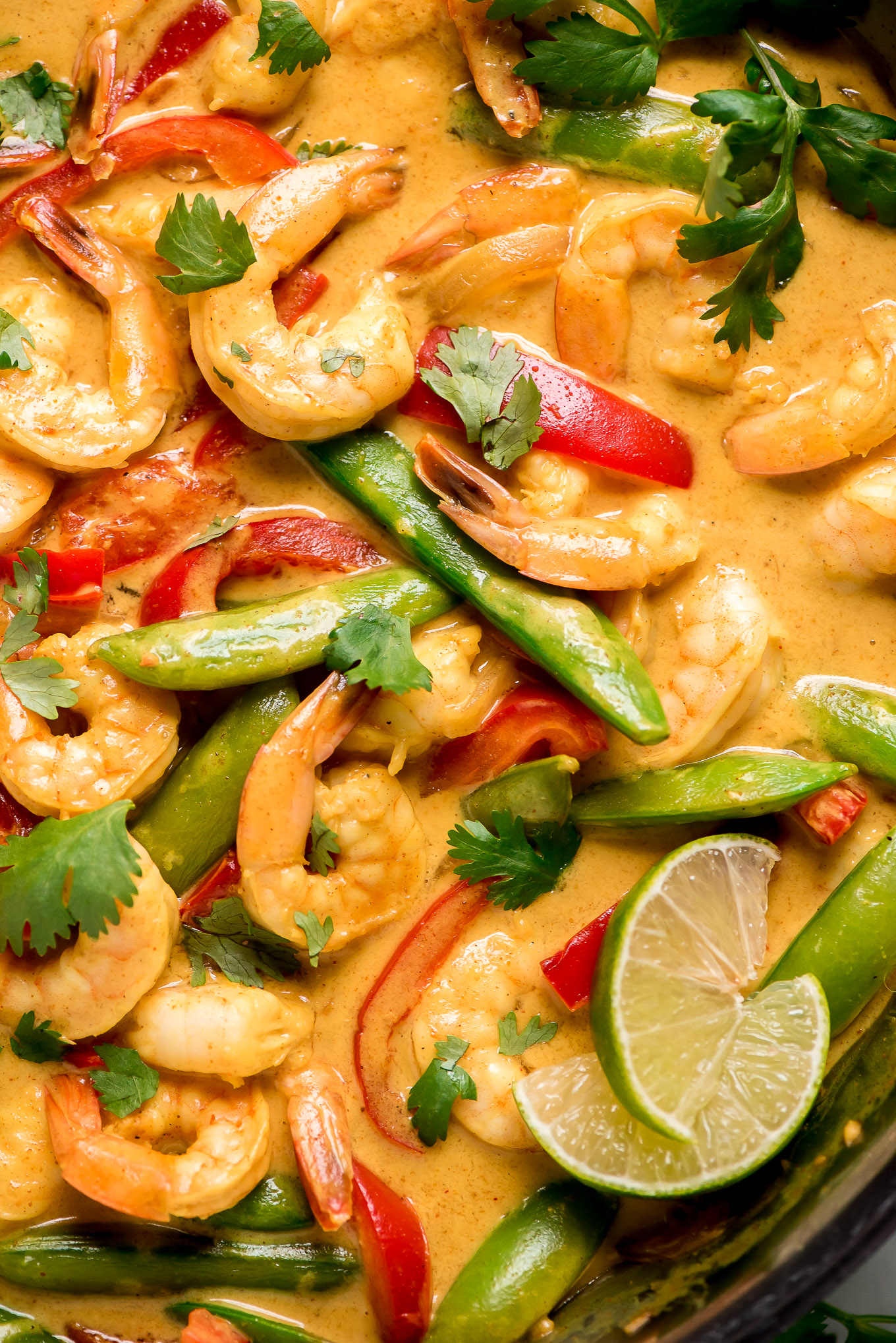 Thai Coconut Shrimp Curry in a pan with red bell peppers, sugar snap peas, cilantro, and lime.