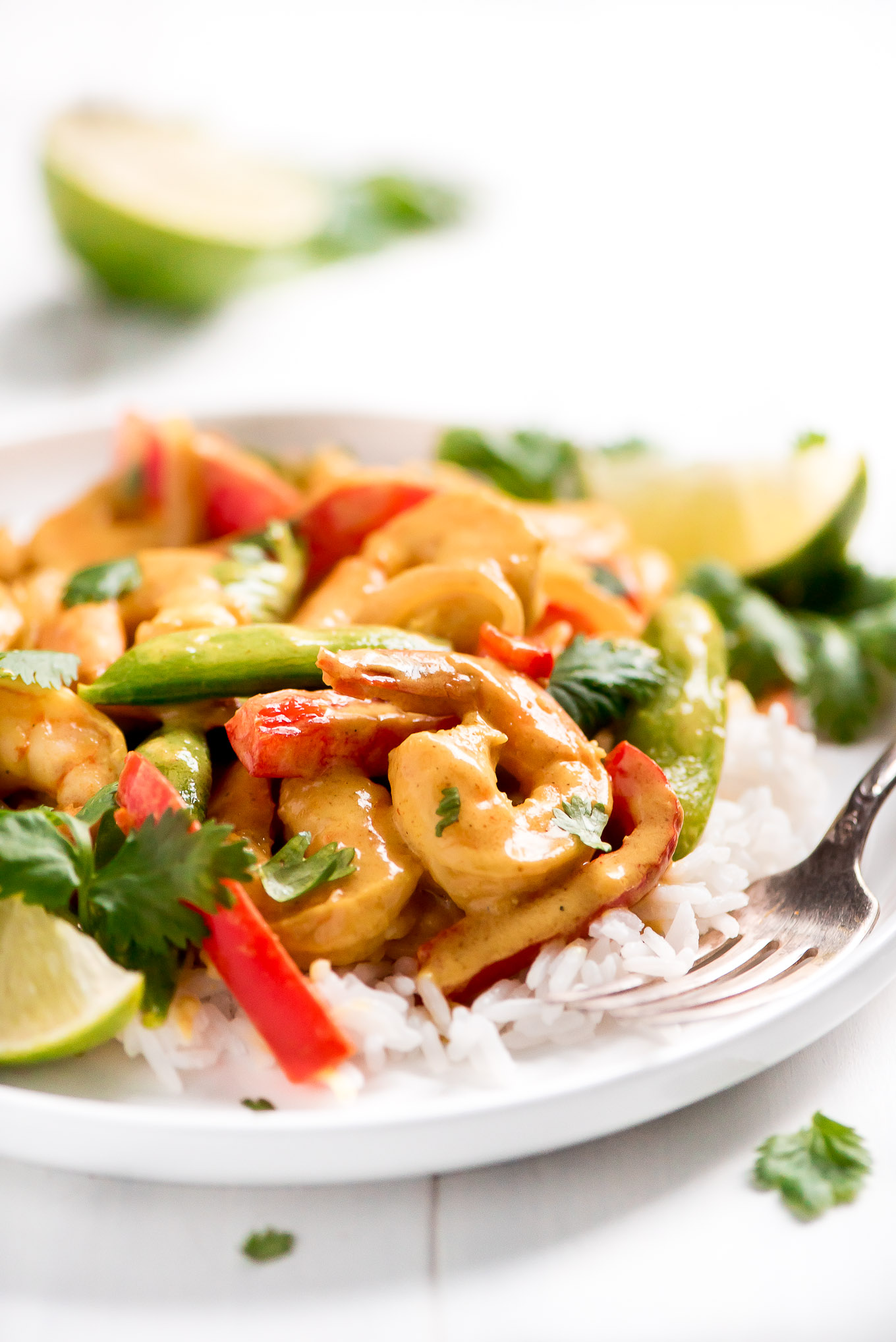 Thai Coconut Curry Shrimp with shrimp, red bell peppers, and sugar snap peas over rice on a plate.