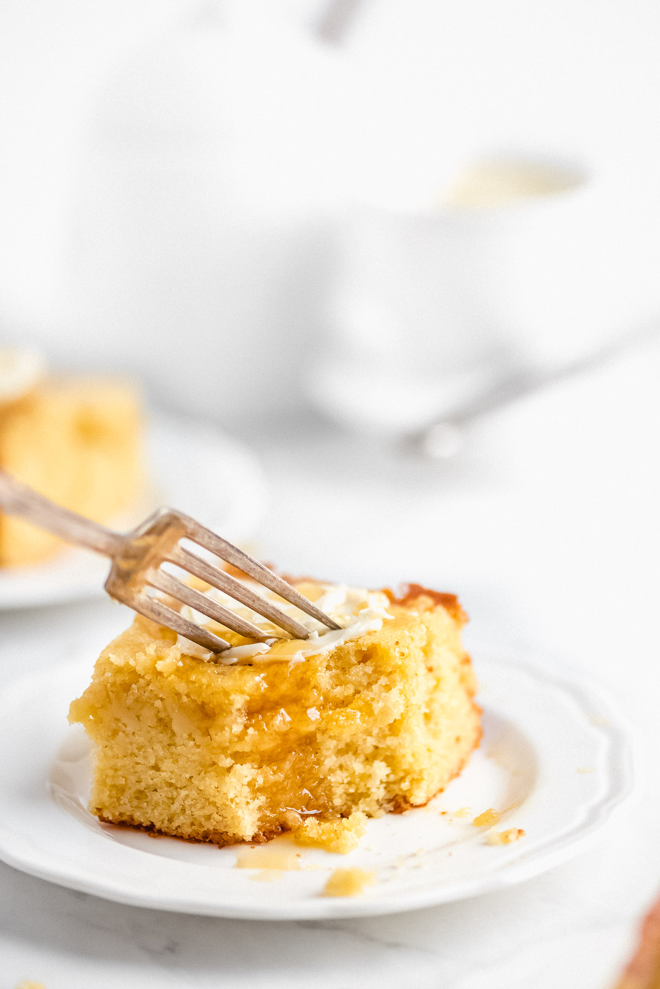 A piece of homemade cornbread on a plate topped with butter and honey and a fork cutting into it.