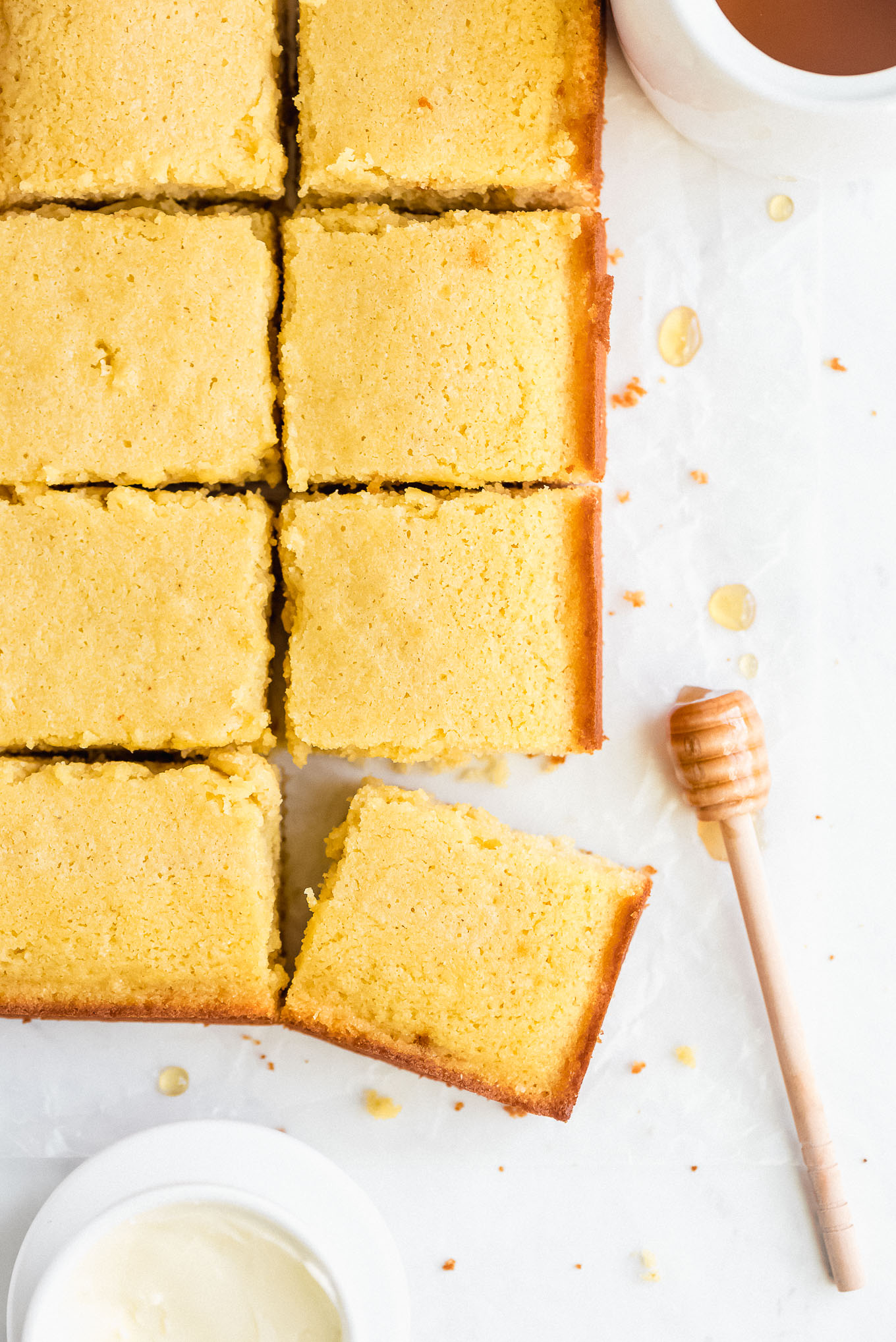 Top view of sliced cornbread, a honey stick, jar of honey, and crock of butter.