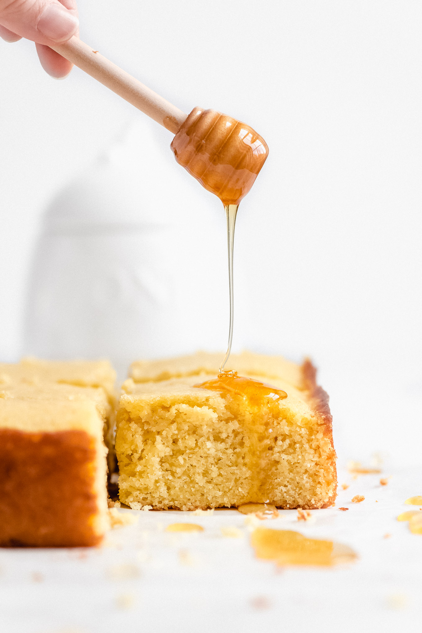 Drizzling golden honey over a piece of tender Buttermilk Cornbread.