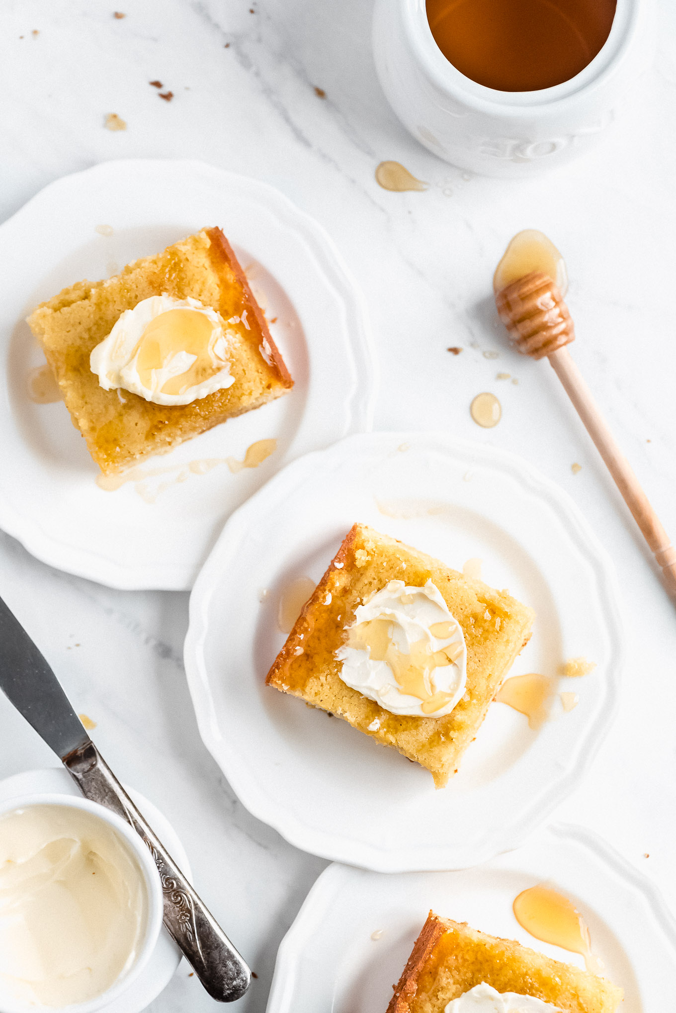 Square pieces of cornbread on plates topped with butter and drizzled with honey.