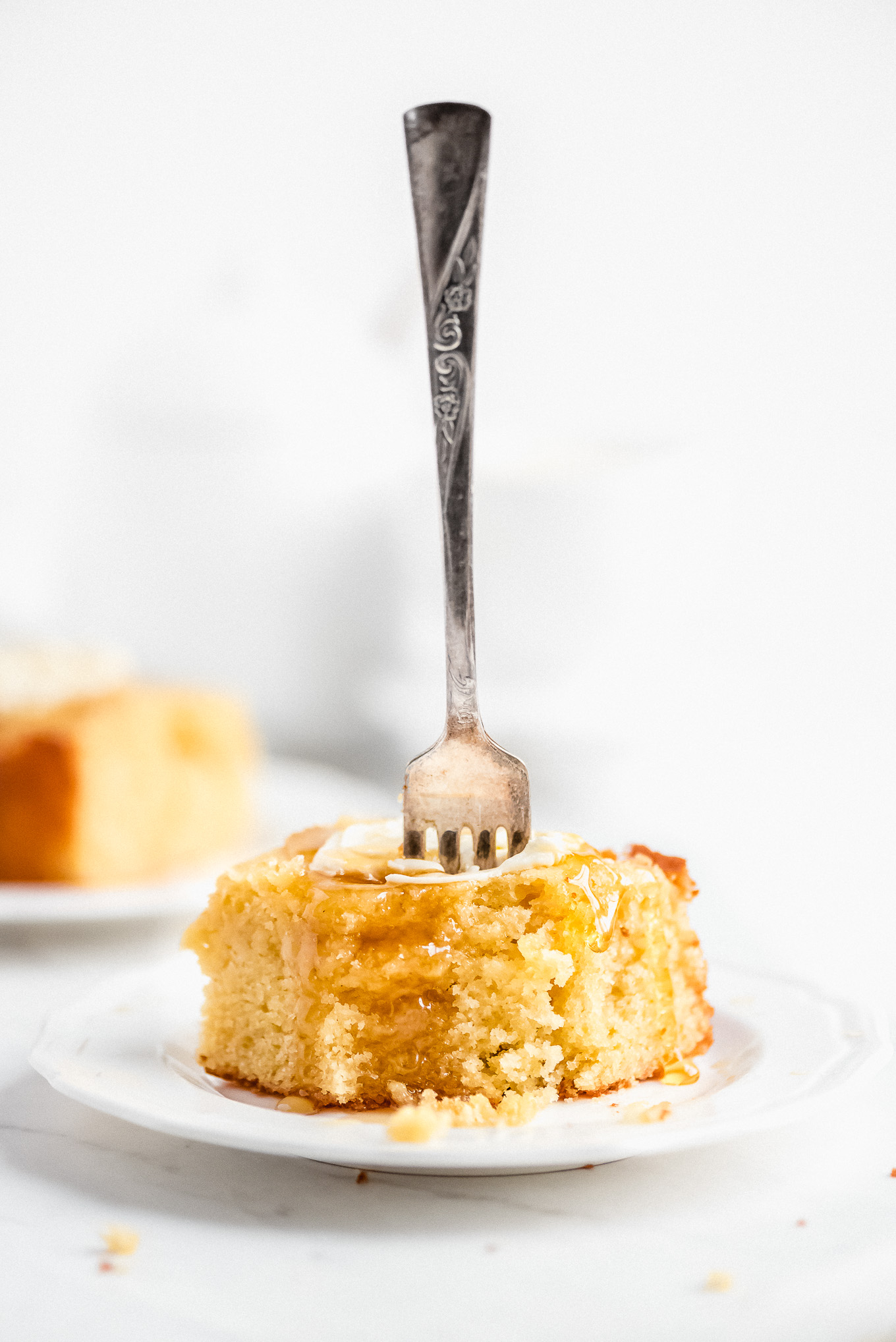 A square piece of buttermilk cornbread with butter and honey on a plate and a fork sticking out of it.