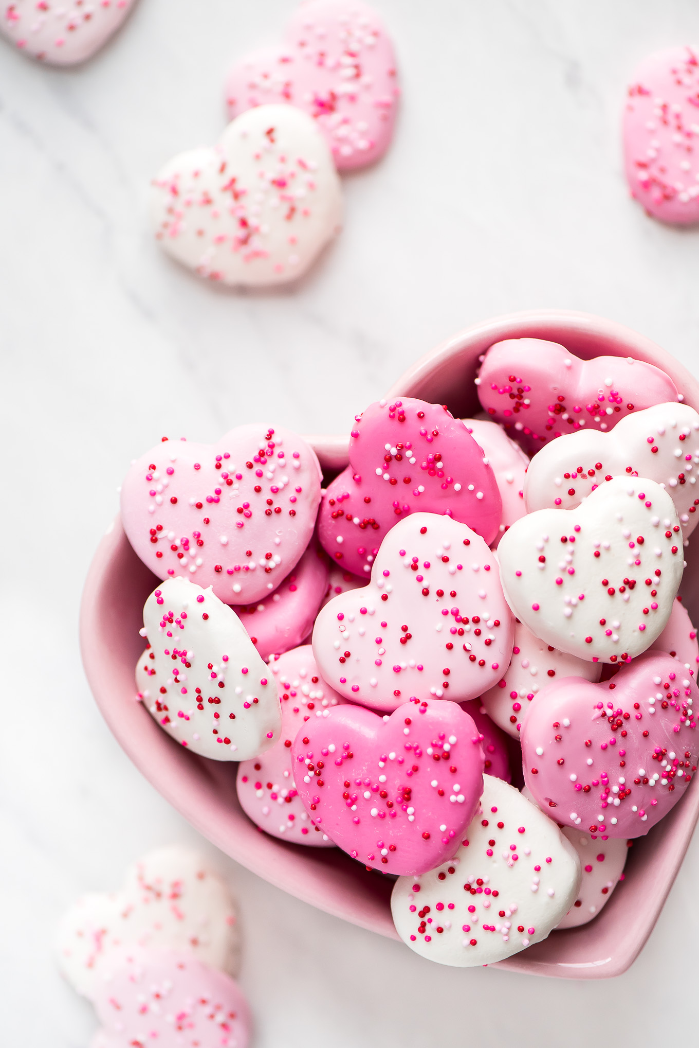 Pink & White Heart Circus Cookies in a heart shaped pink bowl with more cookies surrounding it.