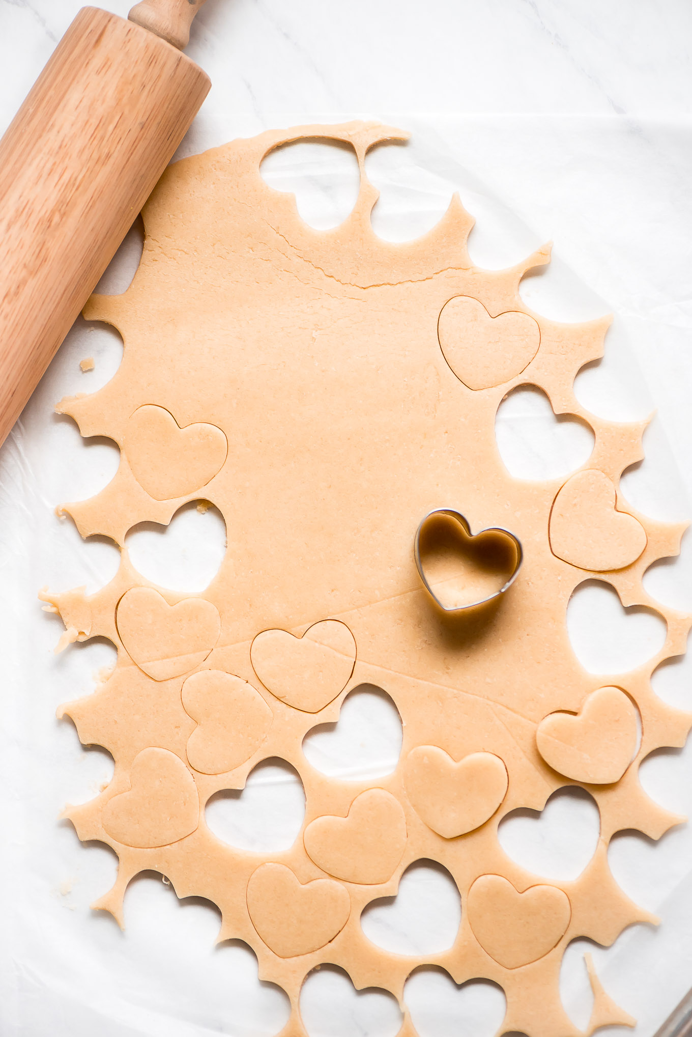 Shortbread cookie dough with heart shaped cookie cutter and some cut out dough already removed.