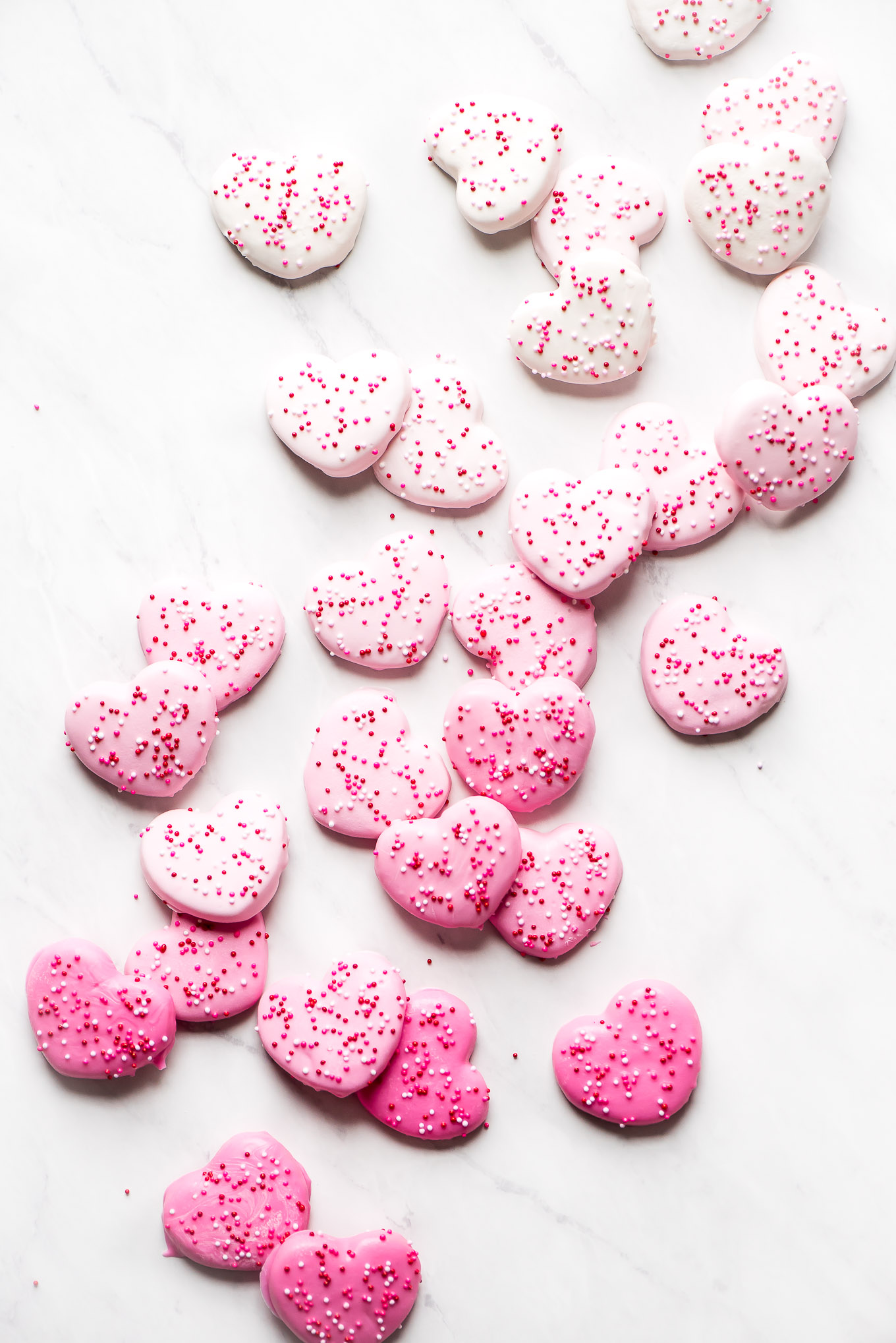 Heart Circus Cookies spread out over the table in a gradient from dark pink to white.