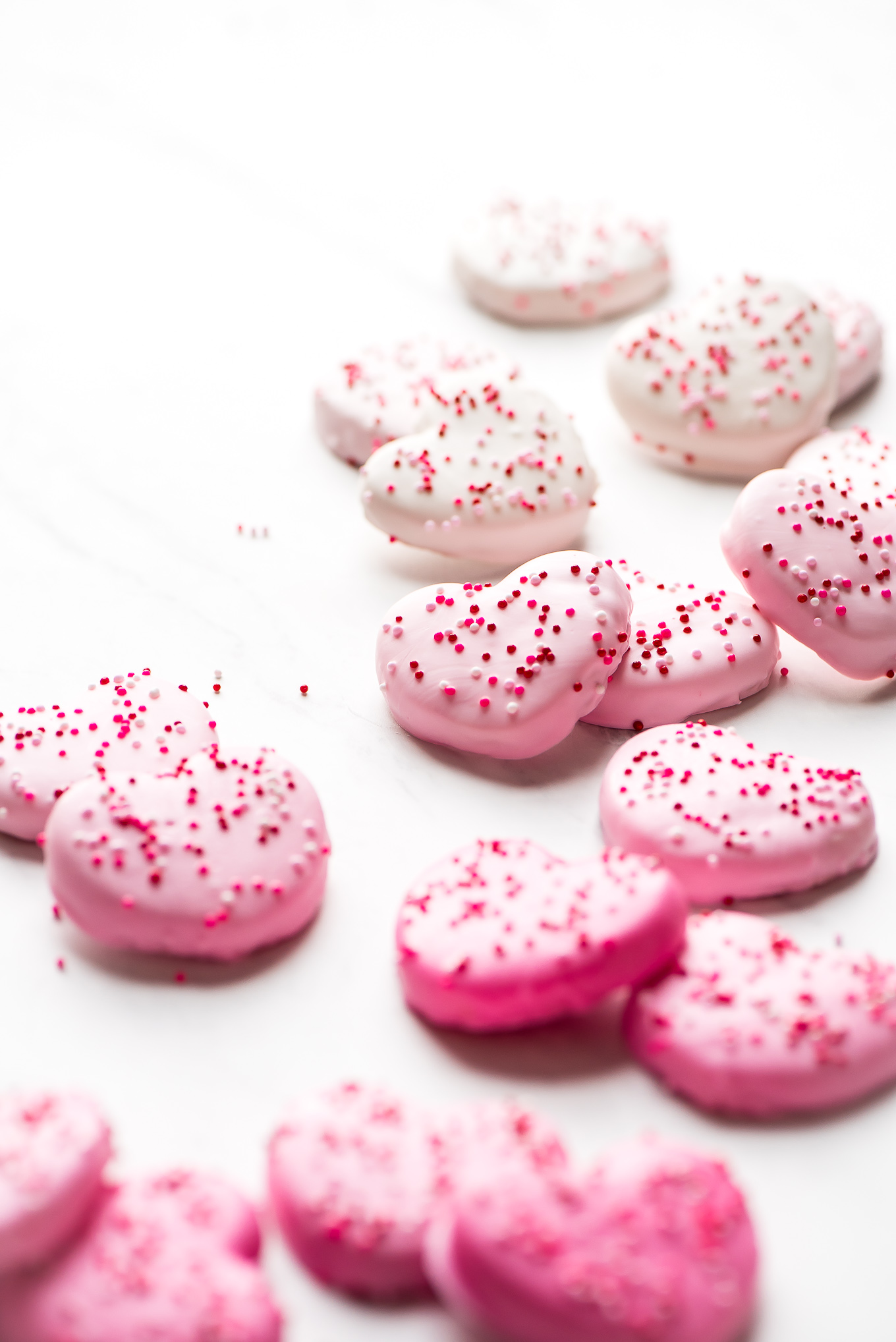 Pink and white Heart Circus Cookies covered in sprinkles spread out on marble surface.