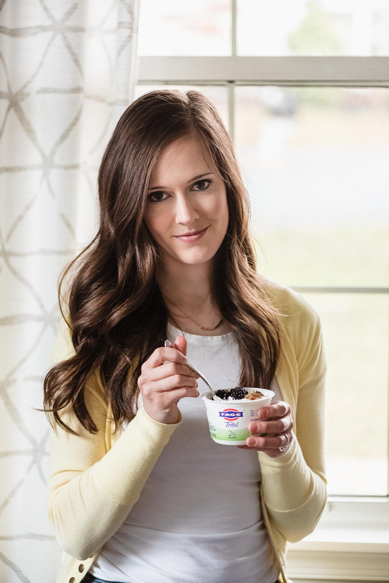 A woman enjoying a container of FAGE Greek yogurt topped with blackberries and granola.
