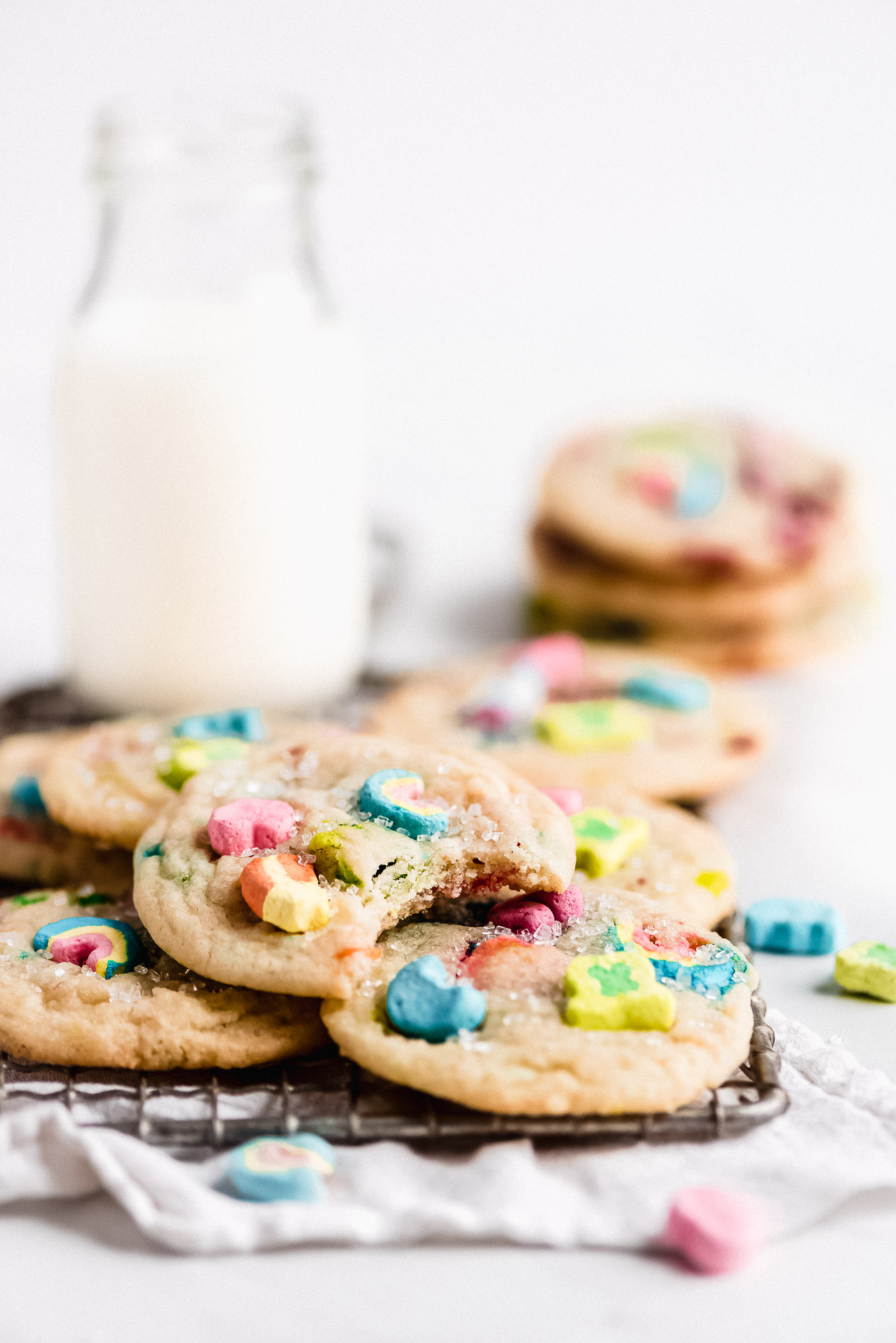 Sugar cookies in a pile on a cooling rack with a jar of milk in the background.