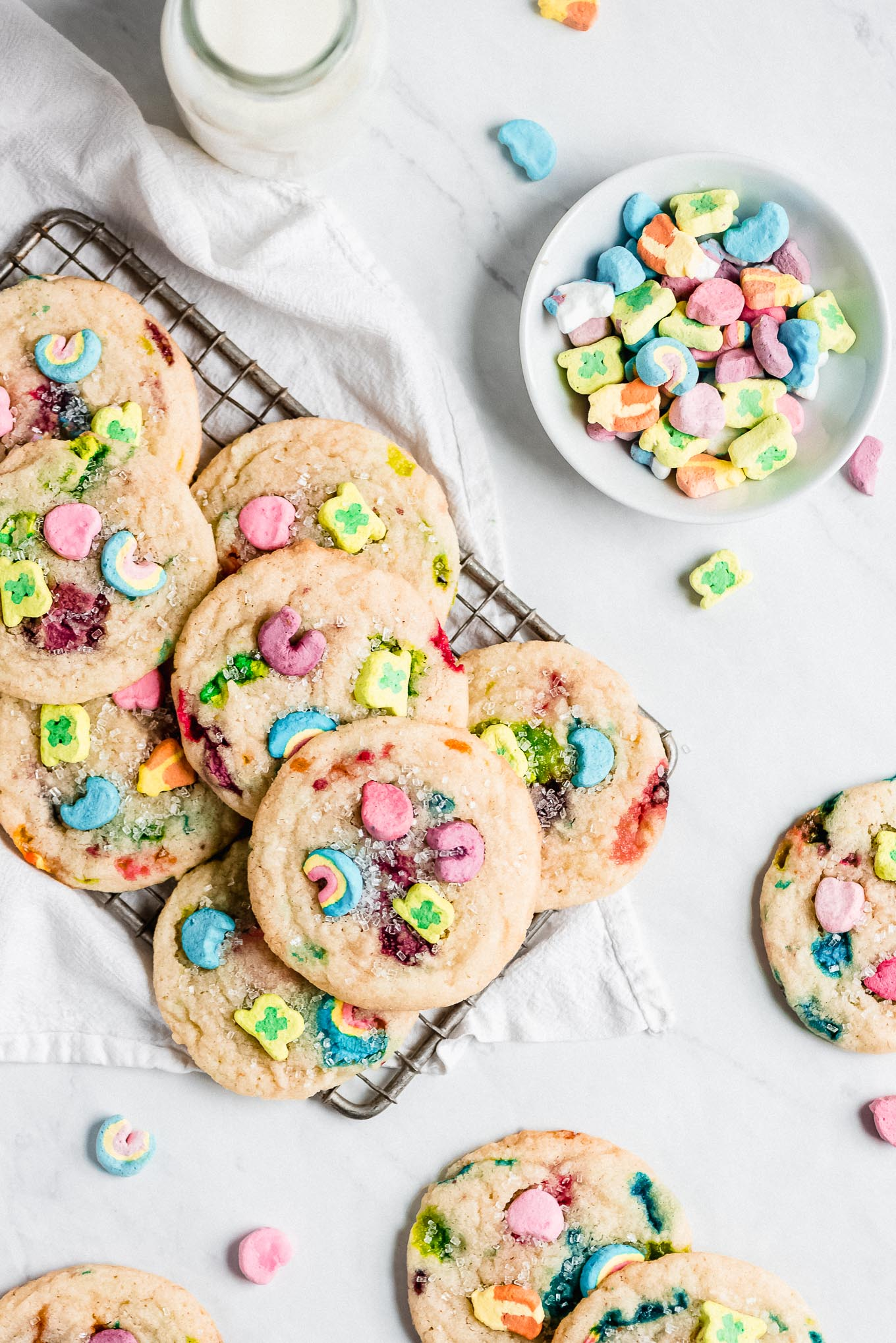 Lucky Charms Cookies on a cooling rack and scattered on surface. A small bowl of colorful marshmallows and a jar of milk.