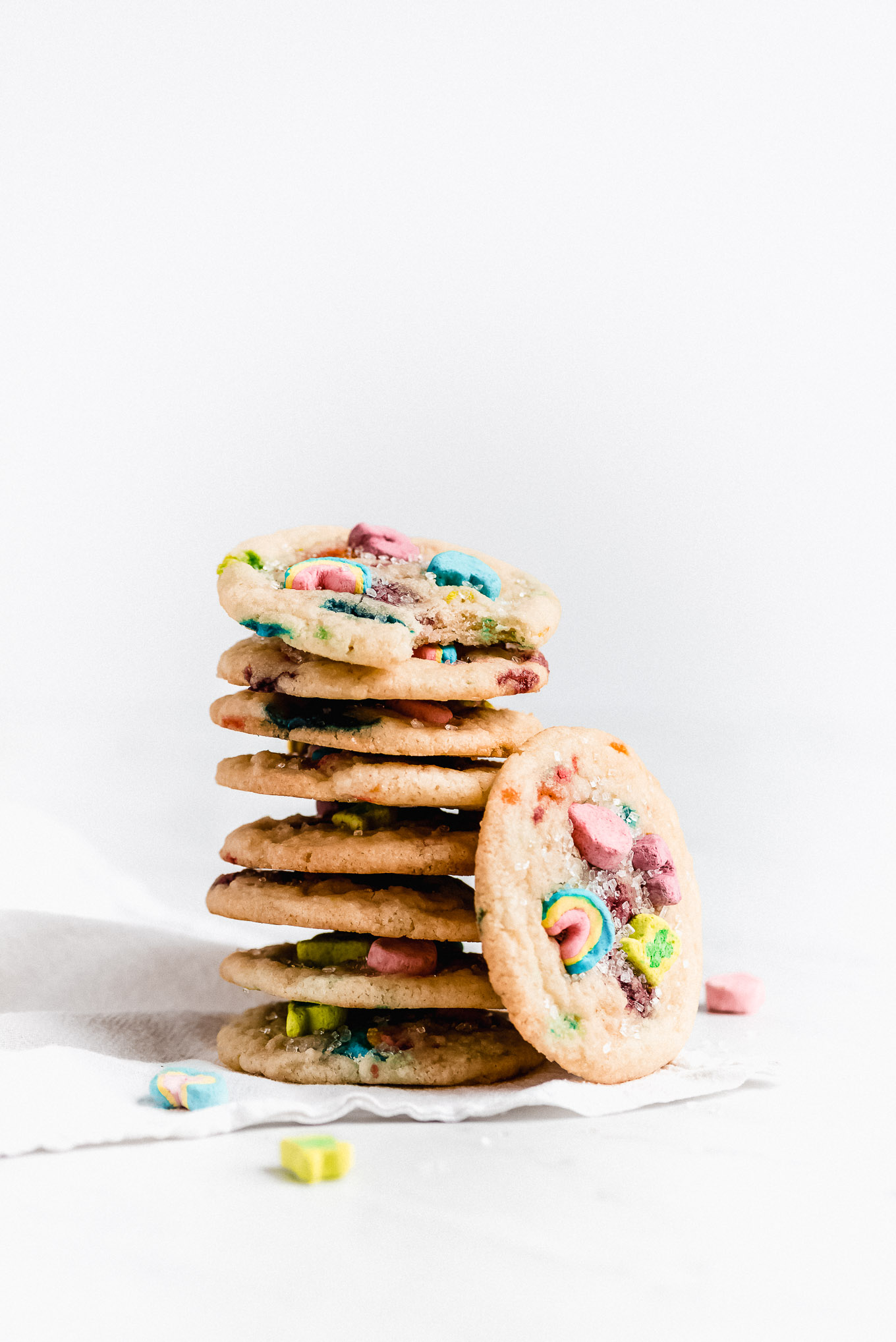 A stack of Lucky Charms Sugar Cookies studded with colorful marshmallows and sparkling with sugar sprinkles.