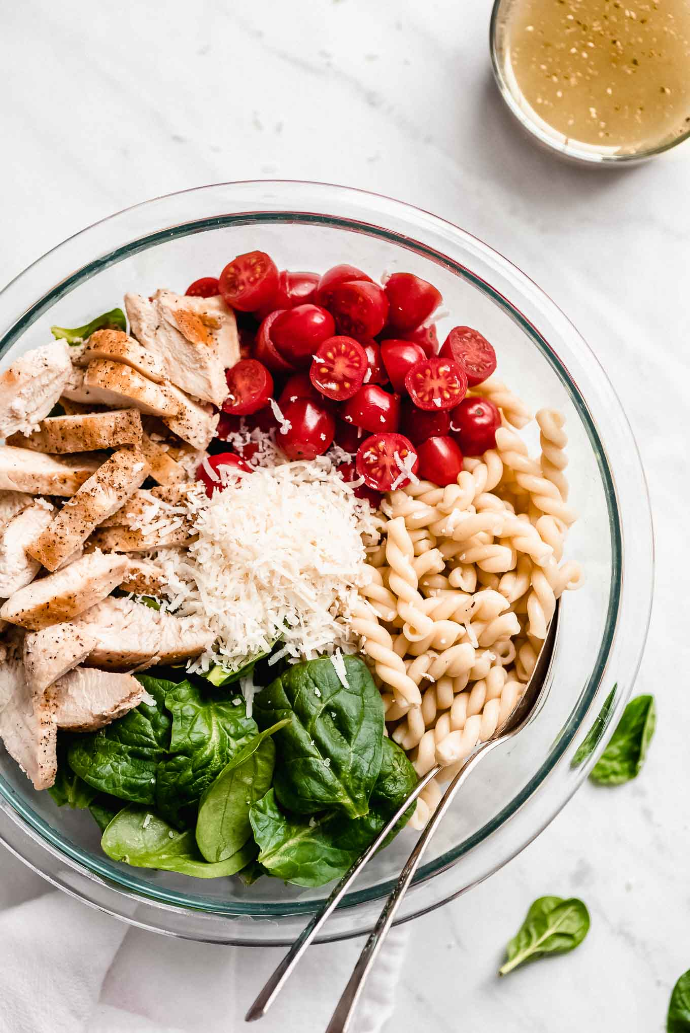 Chicken, tomatoes, noodles, spinach, and Parmesan cheese in a bowl ready to mix together to make Chicken Pasta Salad with Spinach & Tomatoes.