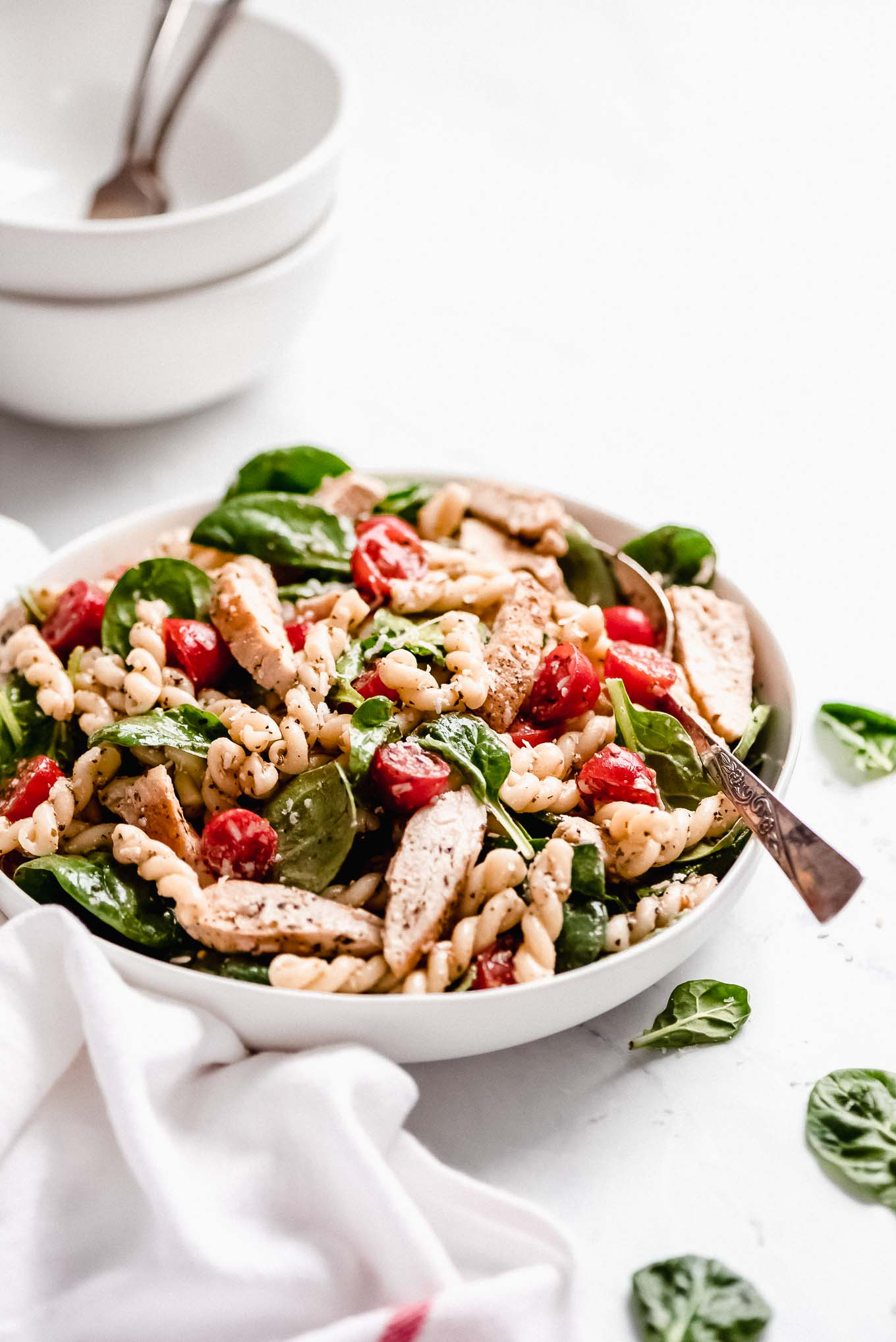 Chicken Pasta Salad with Spinach & Tomatoes in a large bowl with a serving spoon in the side and salad bowls in the background.