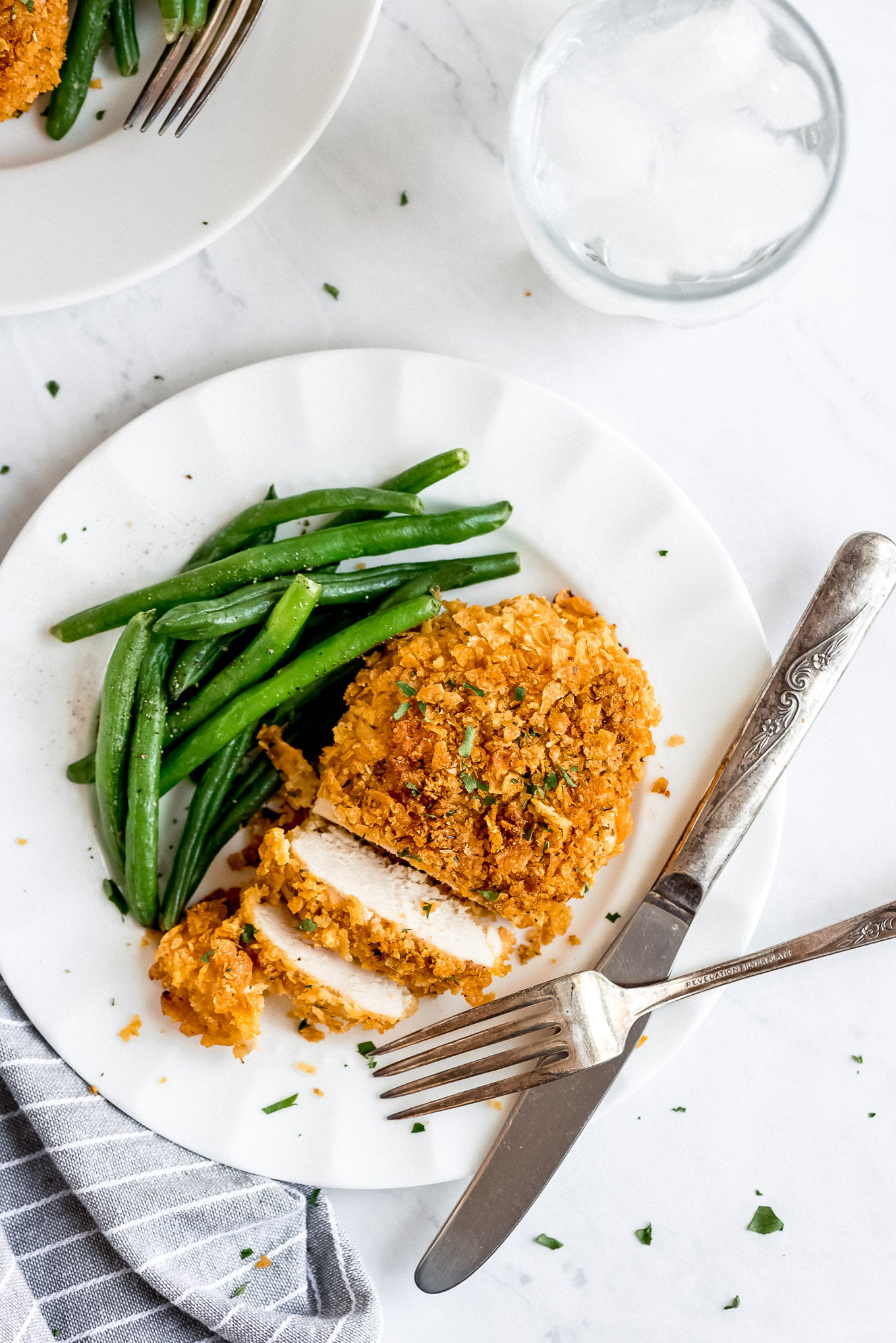 Crispy baked chicken partially sliced on a plate with a side of green beans.