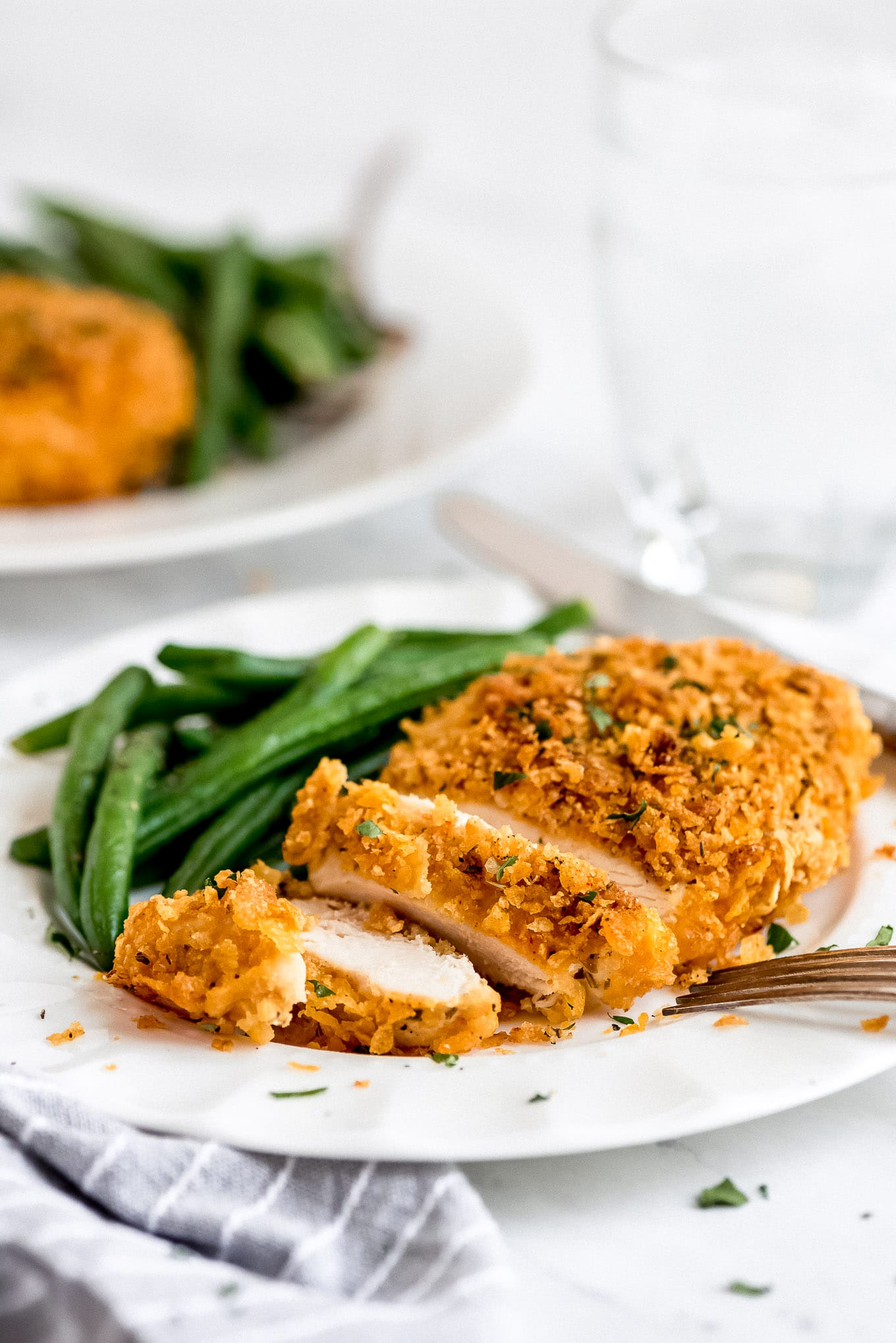 Close up of the crispy baked Cornflake Chicken on a plate with green beans.