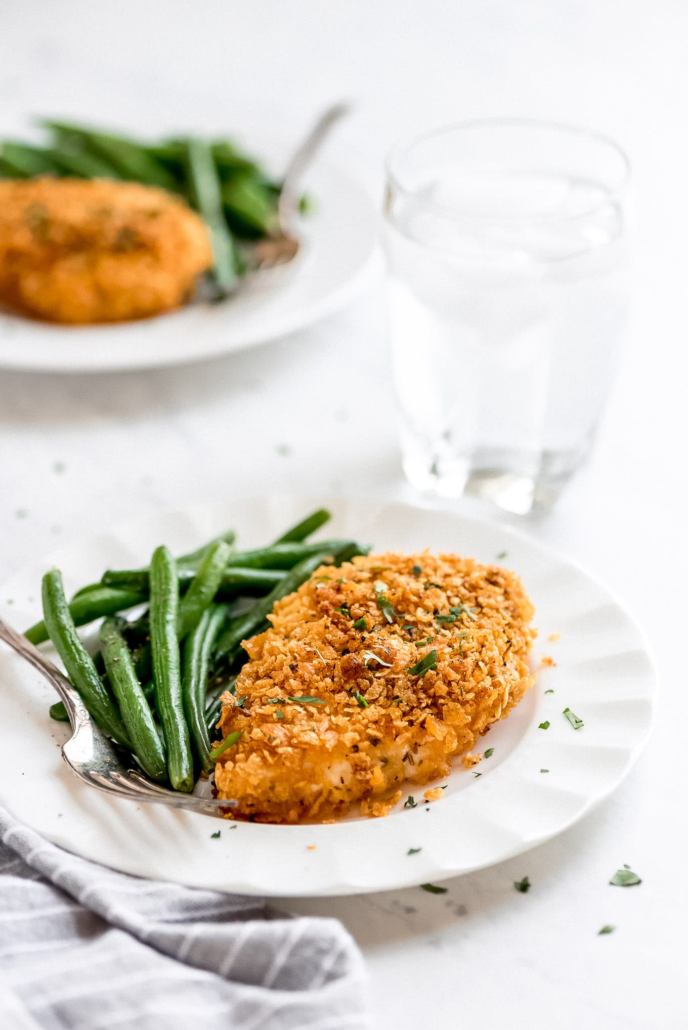 Cornflake Chicken breast on a plate with a side of green beans.