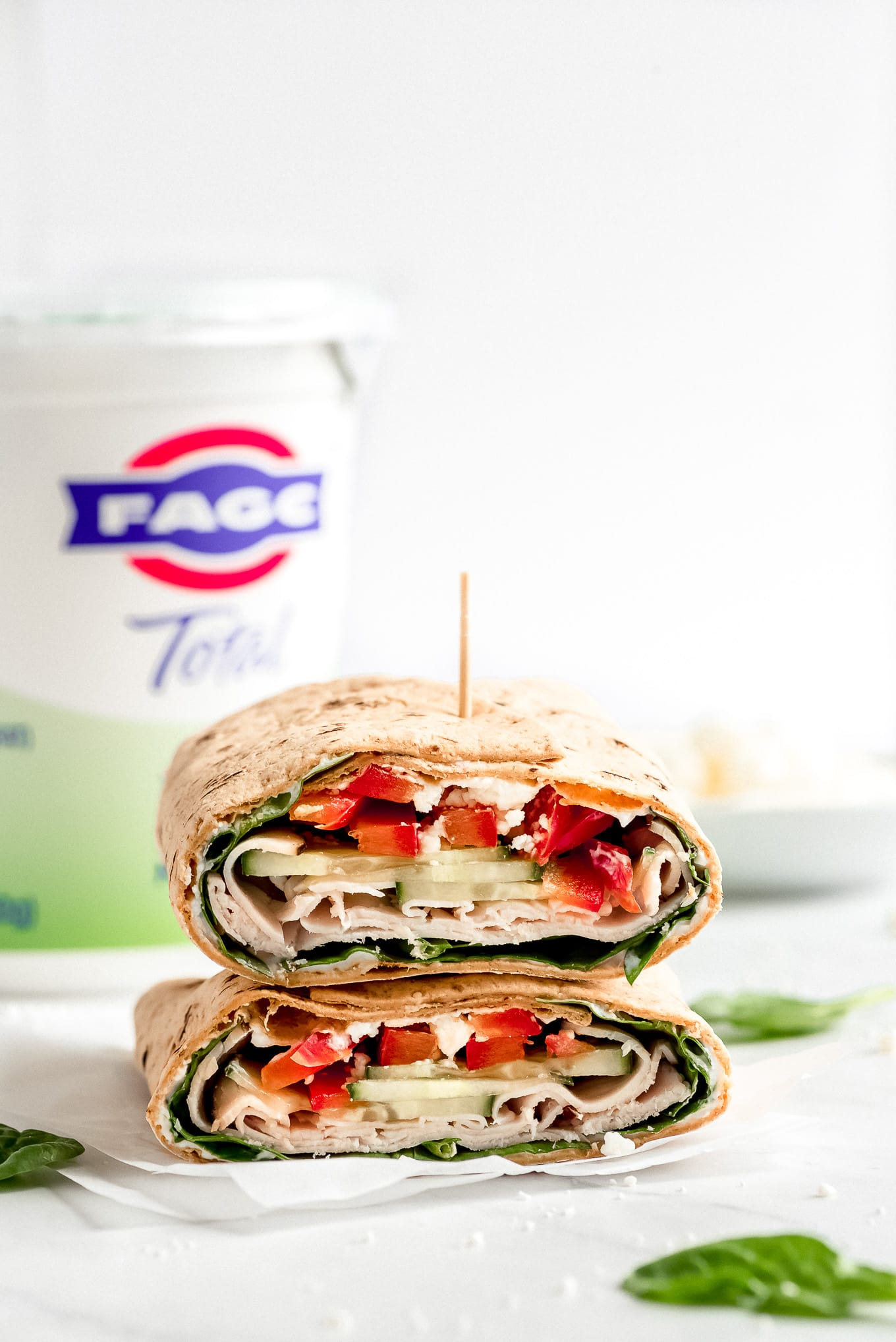Two halves of a Turkey Ranch Wrap are stacked on top of each other showing the inside full of veggies, turkey, and a Greek yogurt ranch sauce.