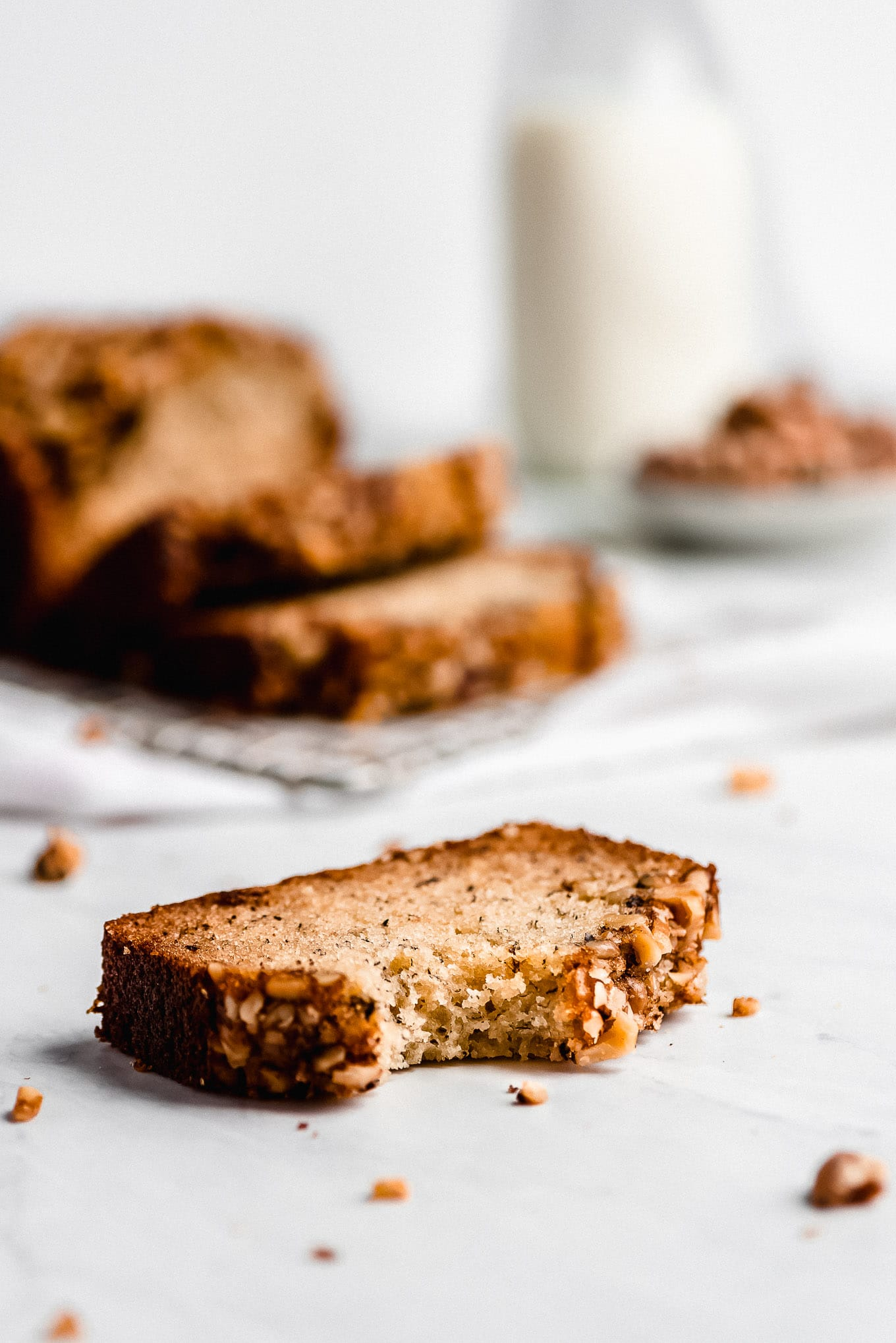 A slice of Banana Nut Bread on the table with a bite taken out showing the fluffy, tender, moist texture.
