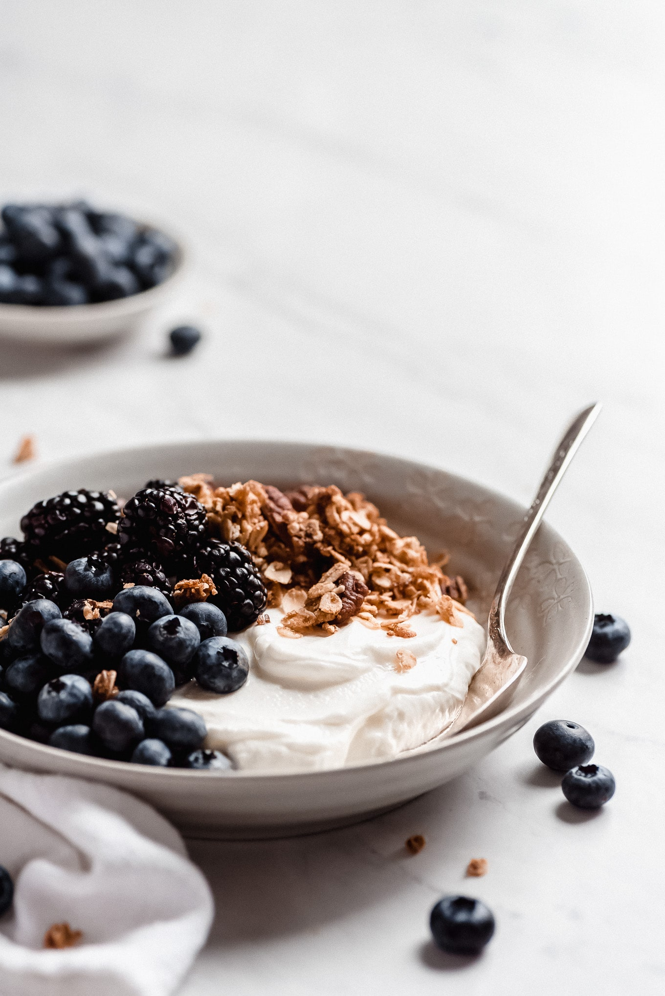 A bowl of plain Greek yogurt, topped with blackberries, blueberries, and granola.