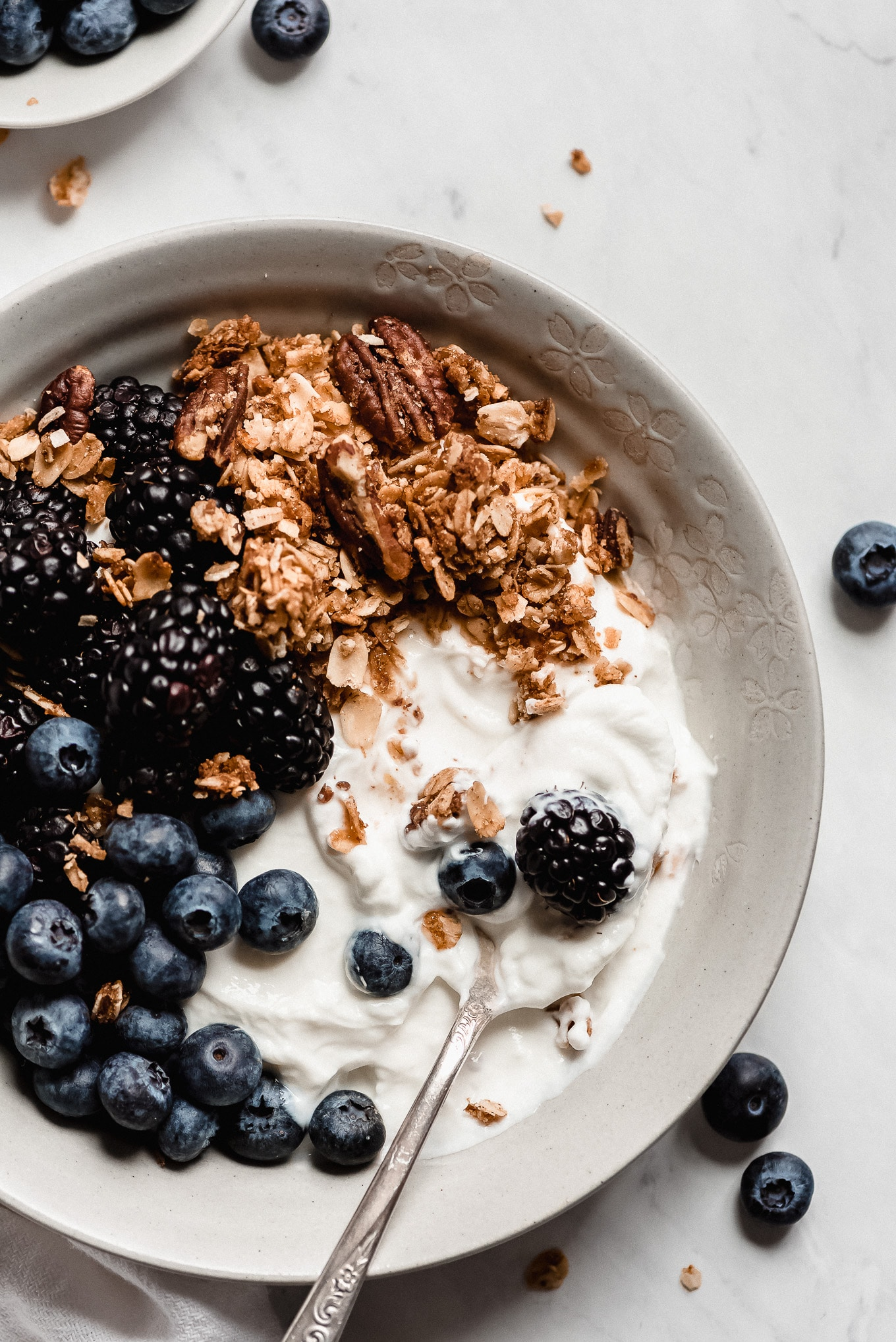 Greek yogurt bowl topped with homemade granola, blueberries, and blackberries.