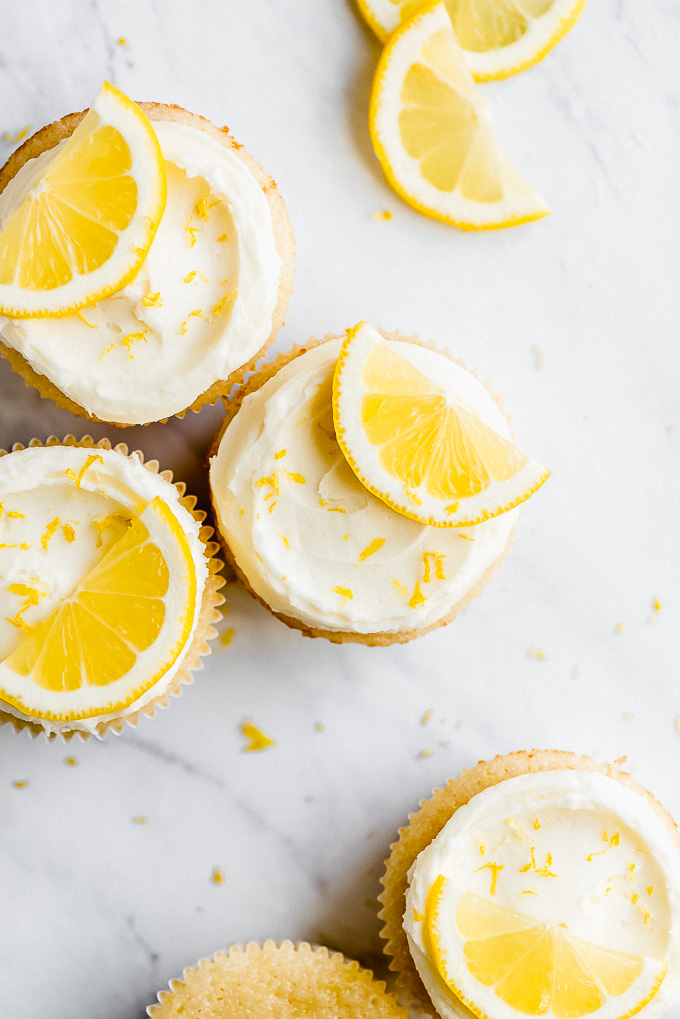 Close up of the top of Lemon Cupcakes garnished with half lemon slices and lemon zest.