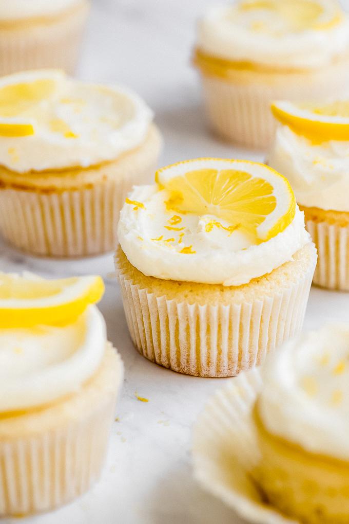 Close up of a Lemon Cupcake with Lemon Buttercream Frosting garnished with half a lemon slice and lemon zest.