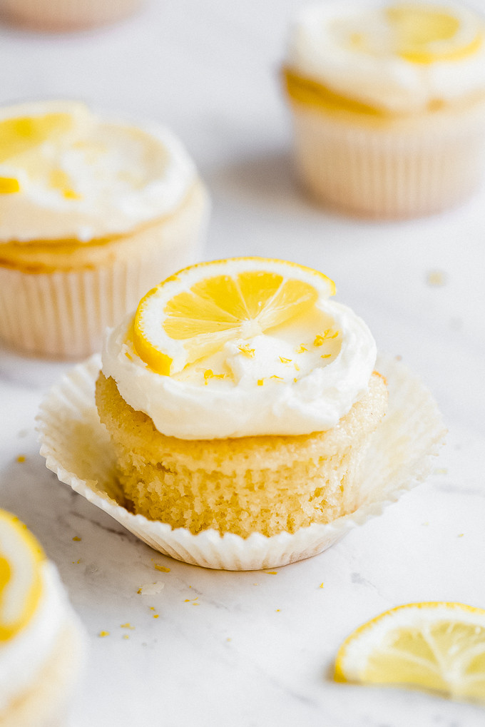 A Lemon Cupcake with Lemon Buttercream Frosting, topped with half a lemon slice, and lemon zest.