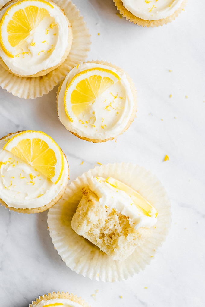 A few Lemon Cupcakes on a marble surface with one on it's side with a bite taken out showing the fluffy texture.