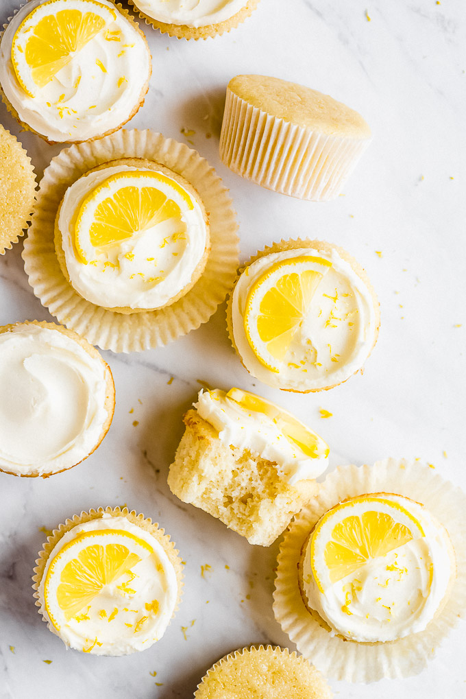 A dozen Lemon Cupcakes topped with lemon buttercream frosting and lemon slices, all spread out on a marble surface.