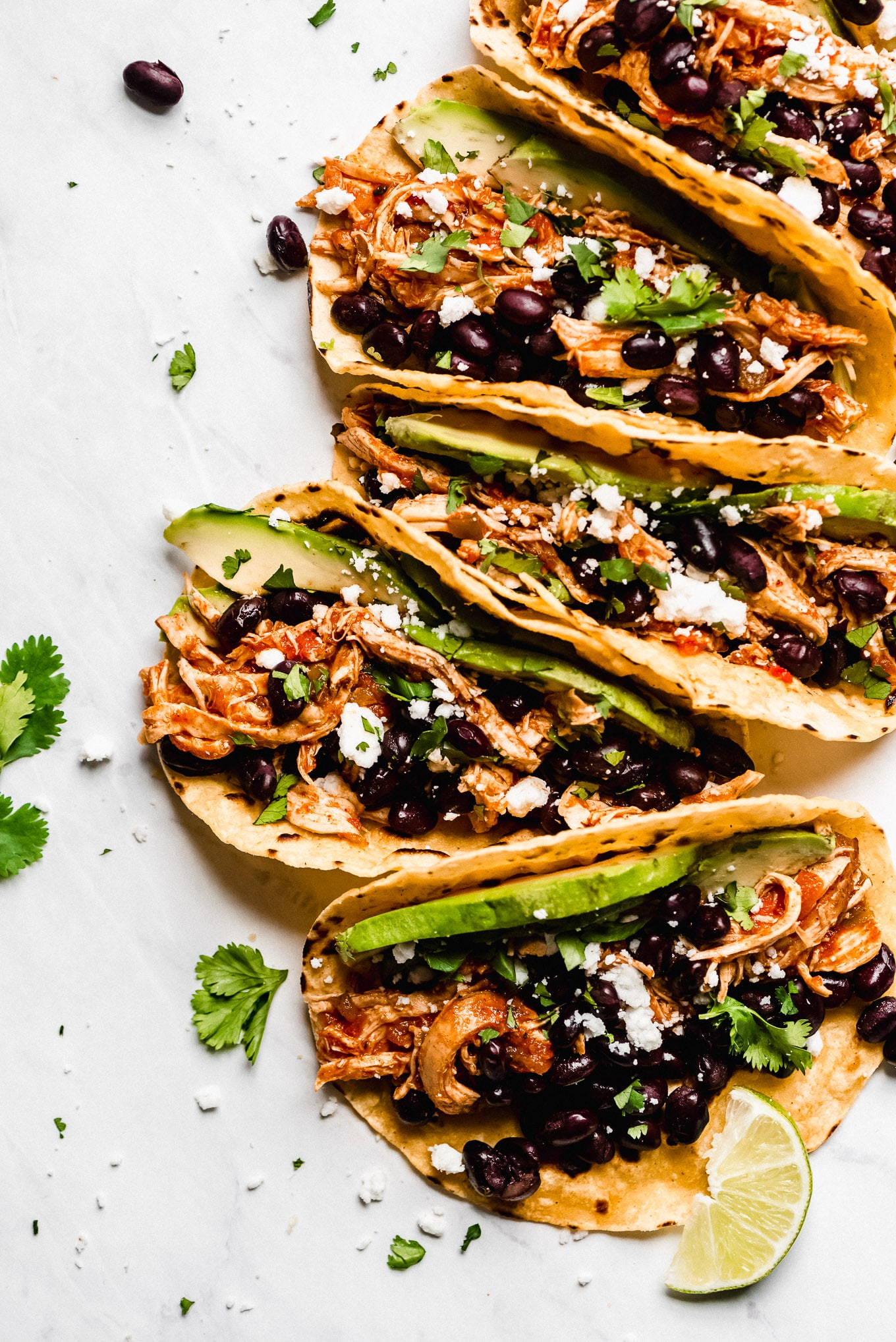 Slow Cooker Salsa Chicken Tacos loaded with black beans, cilantro, avocado, and cheese.