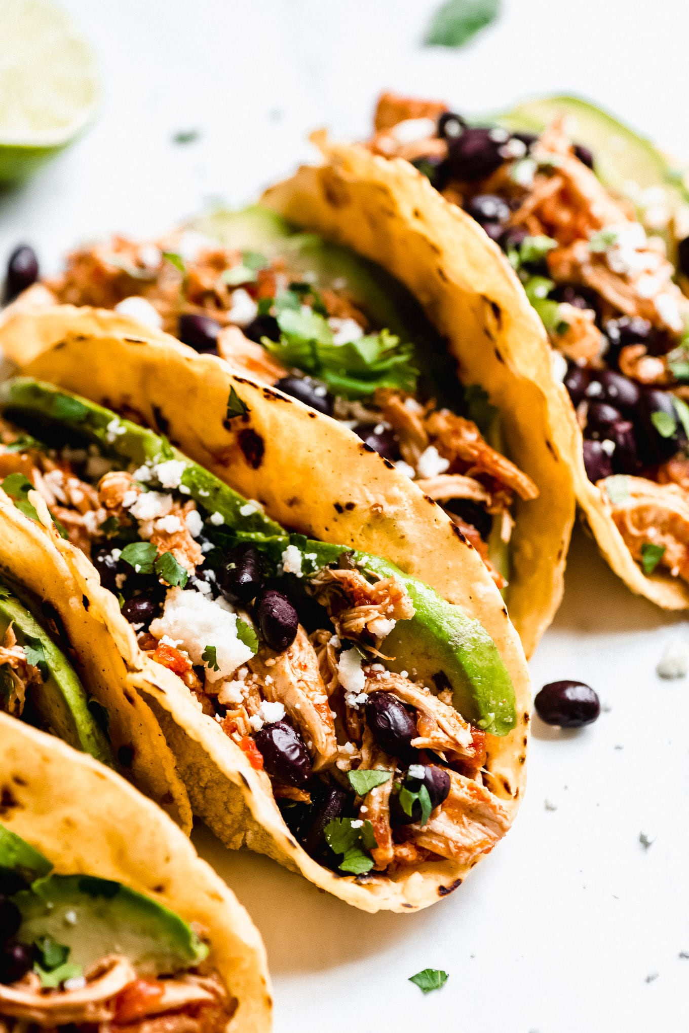 Slow Cooker Salsa Chicken Tacos filled with shredded salsa chicken, black beans, avocados, cilantro, and Queso fresco.