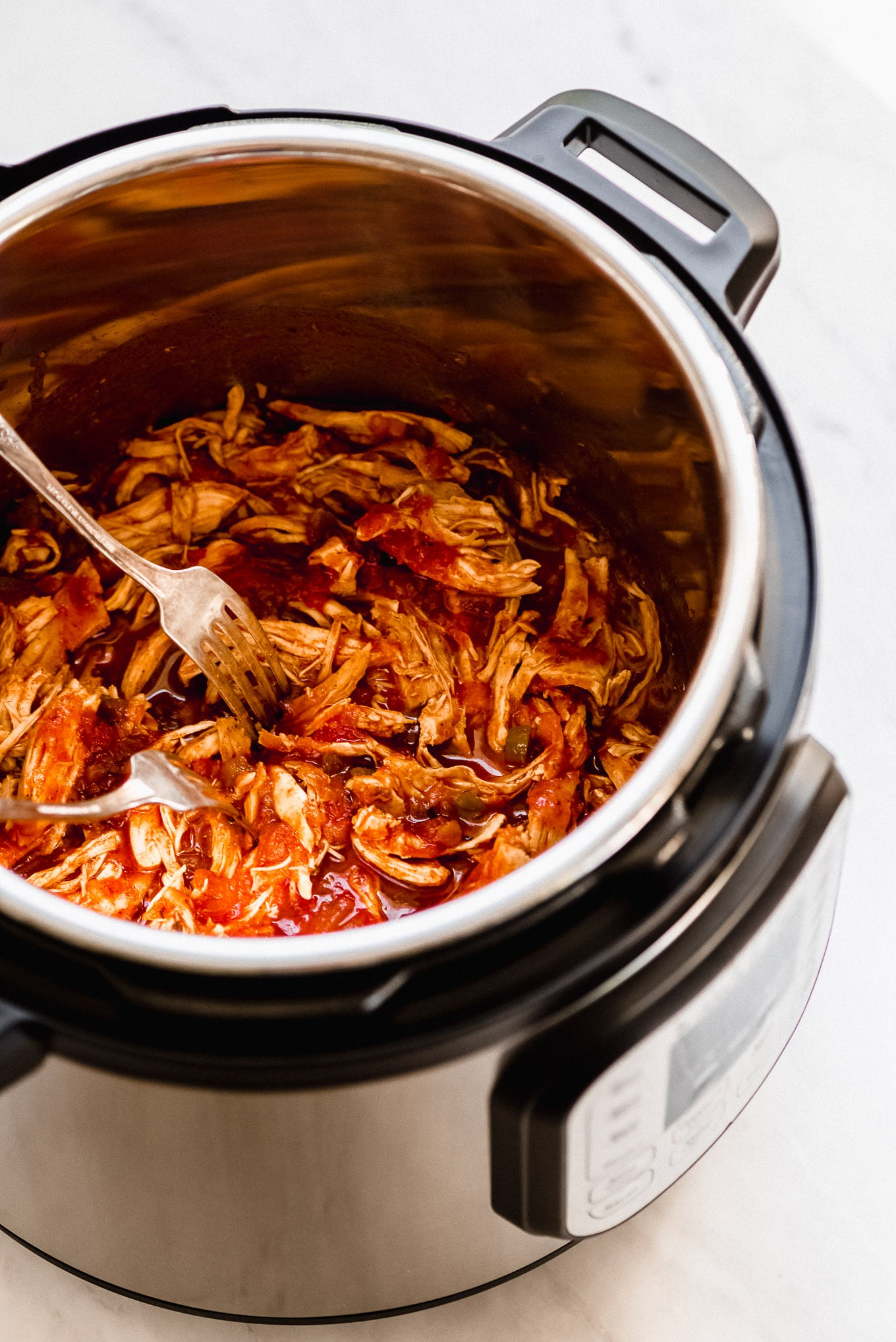 Shredded Instant Pot Salsa Chicken in the pressure cooker.