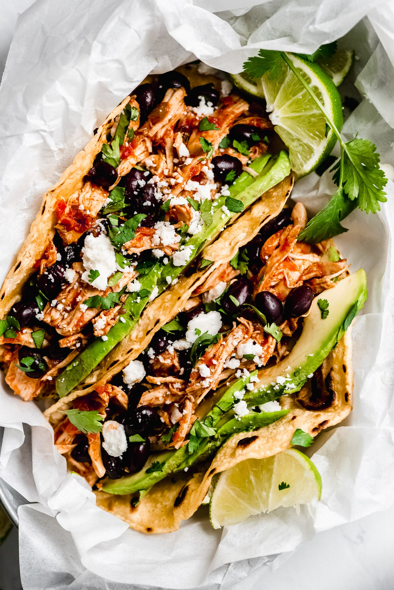 Close up shot of Instant Pot Salsa Chicken Tacos topped with avocado, black beans, cilantro, and cheese.