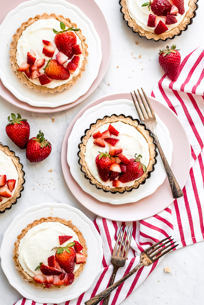 5 Mini Strawberry Tarts on plates with strawberries and forks arranged around them on the table.