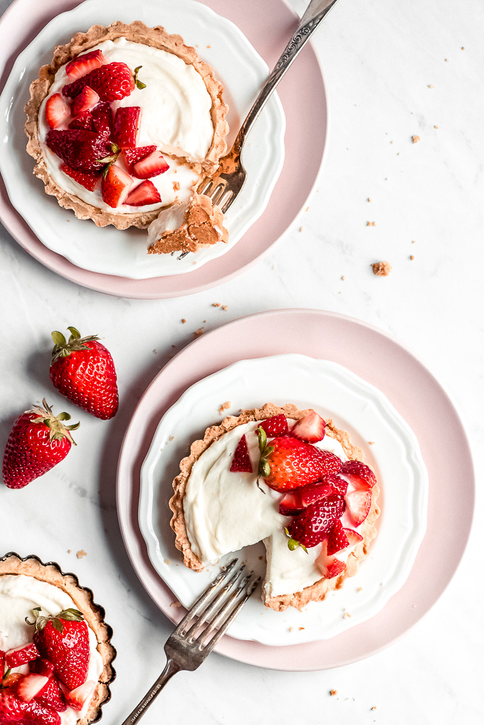 Two Strawberry Tarts on plates with bites taken out and forks on the side.