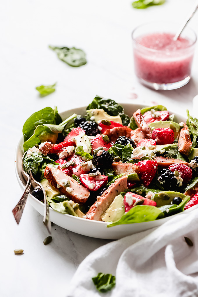 Berry Chicken Spinach Salad all mixed together in a bowl with a cup of poppy seed dressing to the side.