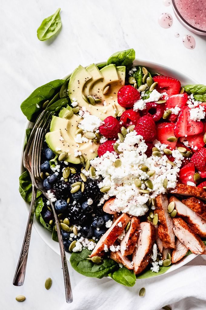 Berry Chicken Spinach Salad in a bowl drizzled with poppy seed dressing.
