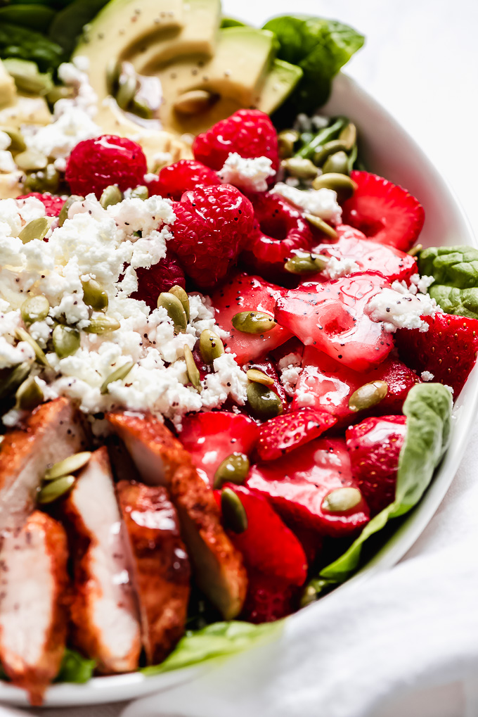 A close up of Berry Chicken Spinach Salad showing off the bright fresh berries topped with poppy seed dressing.