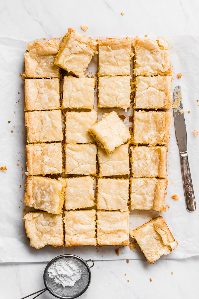 Neiman Marcus Bars or Gooey Butter Cake cut into squares with a knife on the side.