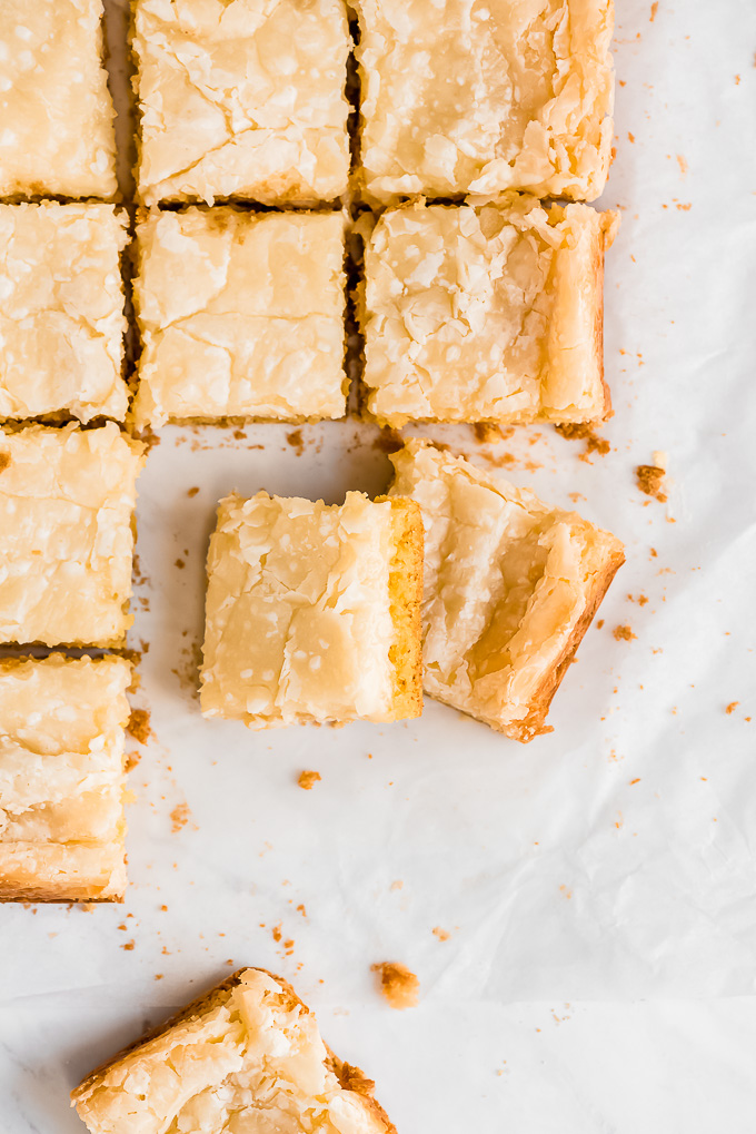 Ooey Gooey Butter Cake Bars cut into squares on parchment paper.