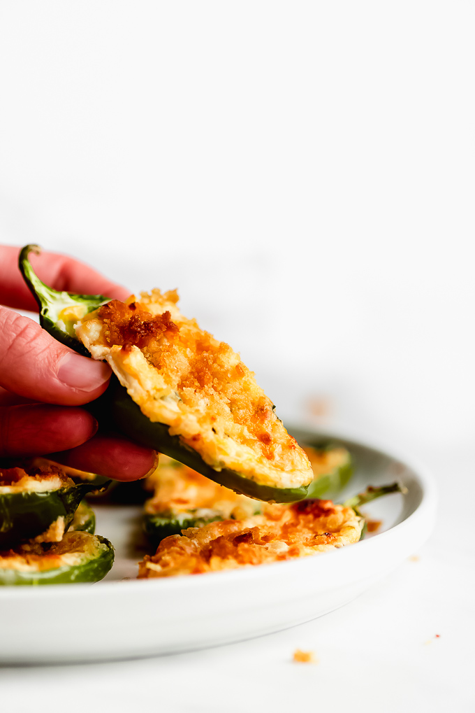 A hand picking up a Jalapeño Popper from a plate.