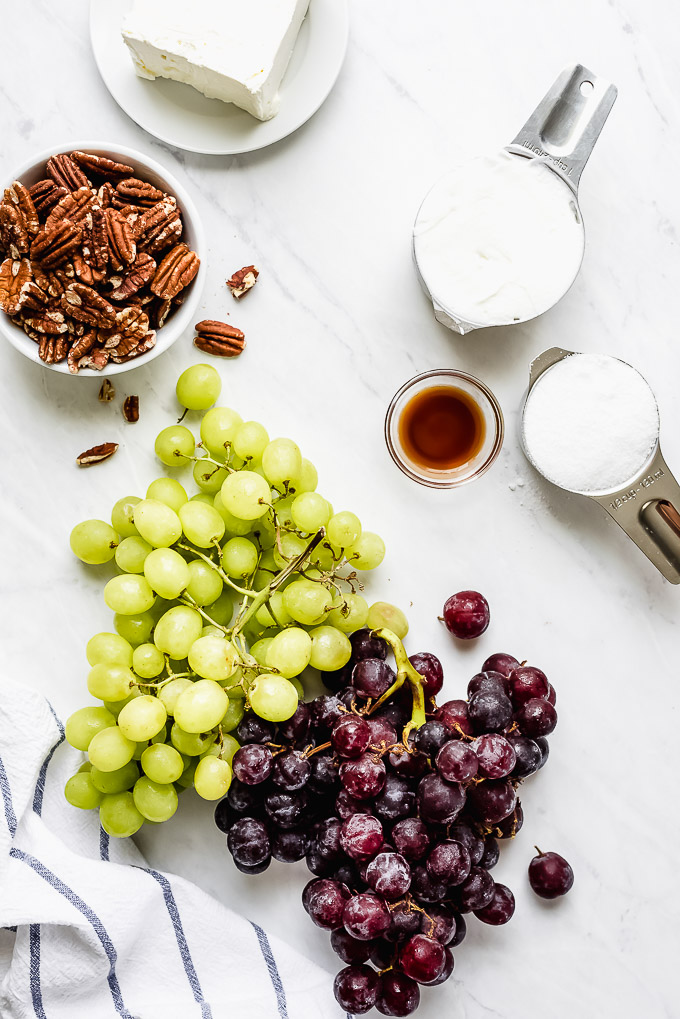 Grapes, pecans, cream cheese, Greek yogurt, sugar, and vanilla on a marble surface.