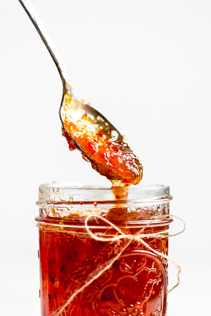 A close up shot of a spoonful of Jalapeño Pepper Jelly being lifted out of a jar and dripping back down into it.