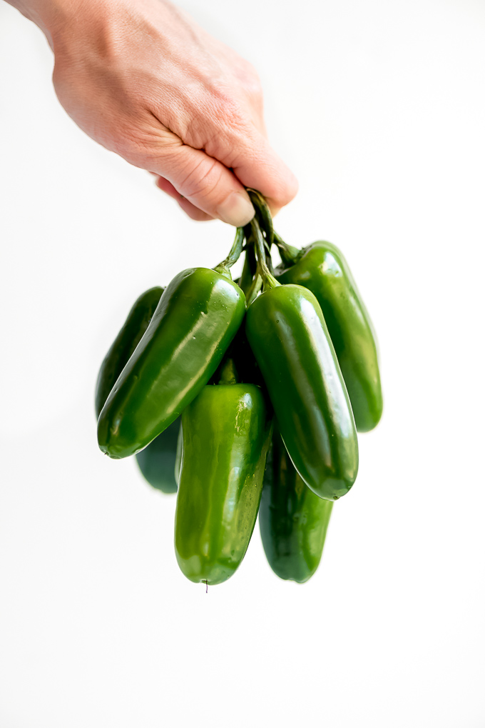 A hand holding a bunch of Jalapeños.