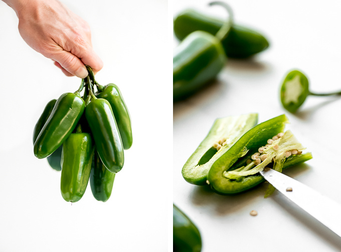 A hand holding a bunch of jalapenos and a jalapeno cut in half showing seeds and veins being cut out.